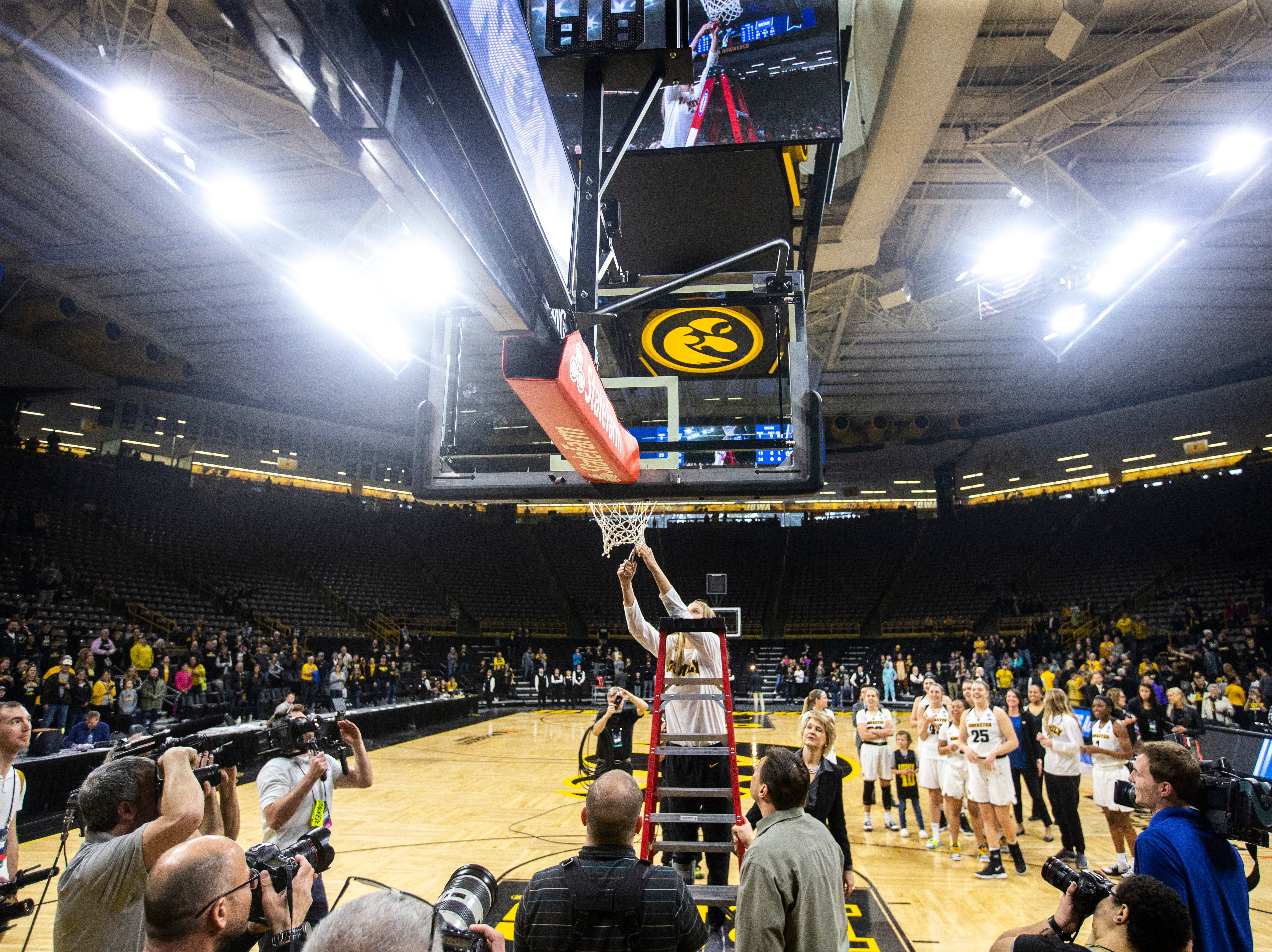 Iowa forward Logan Cook (23) cuts down the nets on the court after a NCAA women's basketball tournament second-round game, Sunday, March 24, 2019, at Carver-Hawkeye Arena in Iowa City, Iowa.