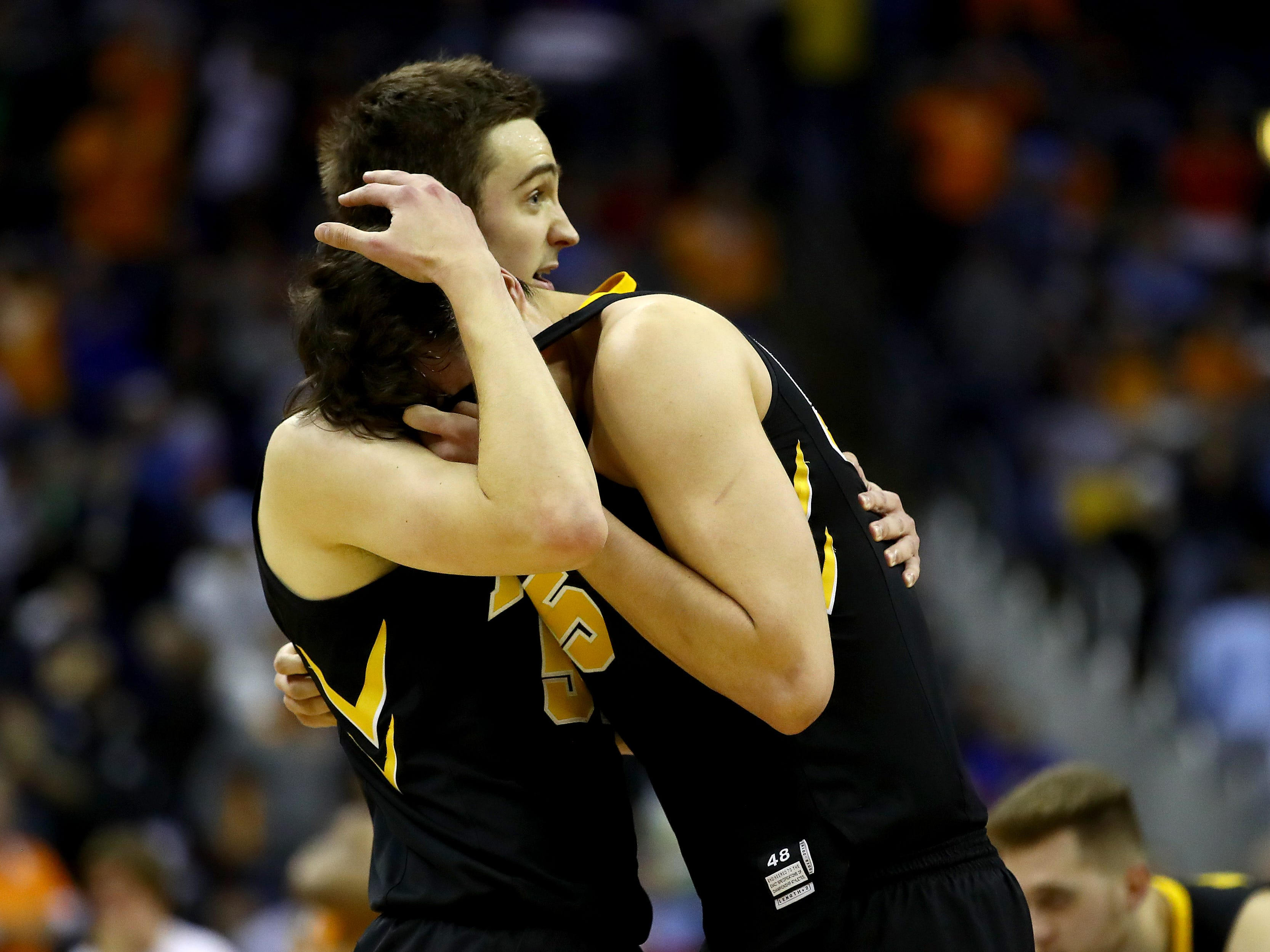Iowa senior Nicholas Baer, left, and Luka Garza embrace following the Hawkeyes' 83-77 overtime loss to Tennessee.