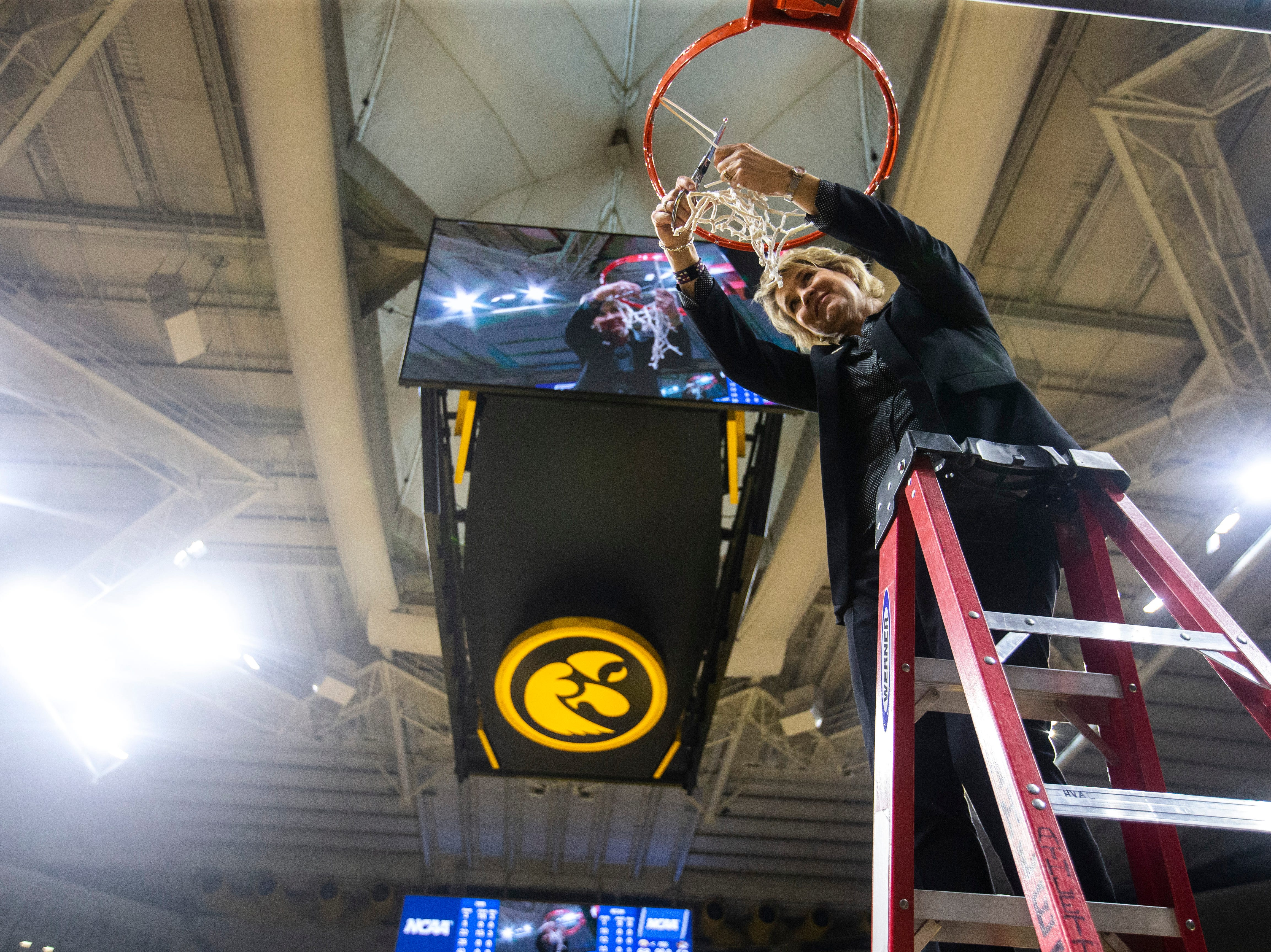 Iowa head coach Lisa Bluder cuts down the nets on the court after a NCAA women's basketball tournament second-round game, Sunday, March 24, 2019, at Carver-Hawkeye Arena in Iowa City, Iowa.