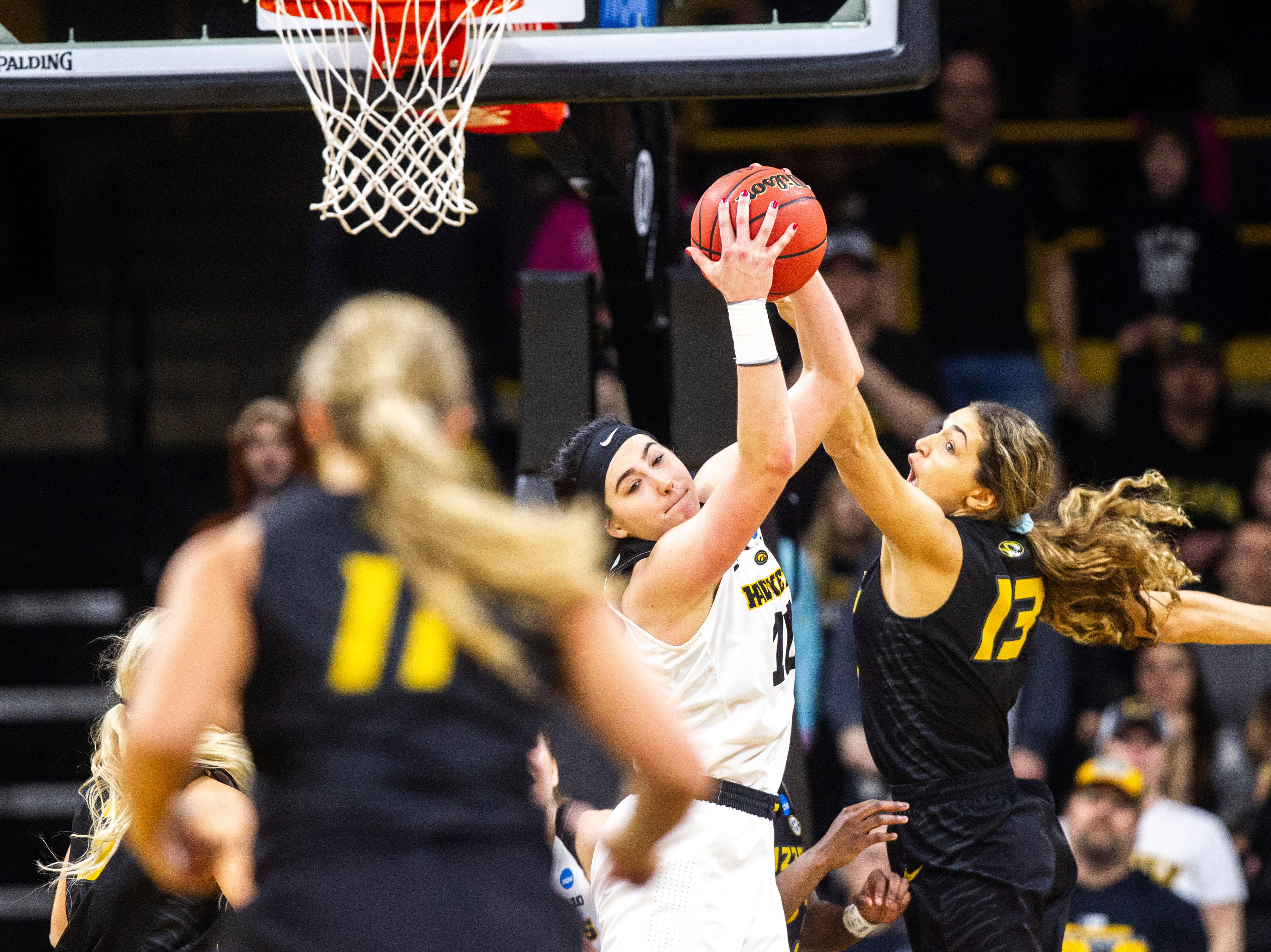 Iowa center Megan Gustafson (10) grabs a rebound against Missouri forward Hannah Schuchts (13) during a NCAA women's basketball tournament second-round game, Sunday, March 24, 2019, at Carver-Hawkeye Arena in Iowa City, Iowa.