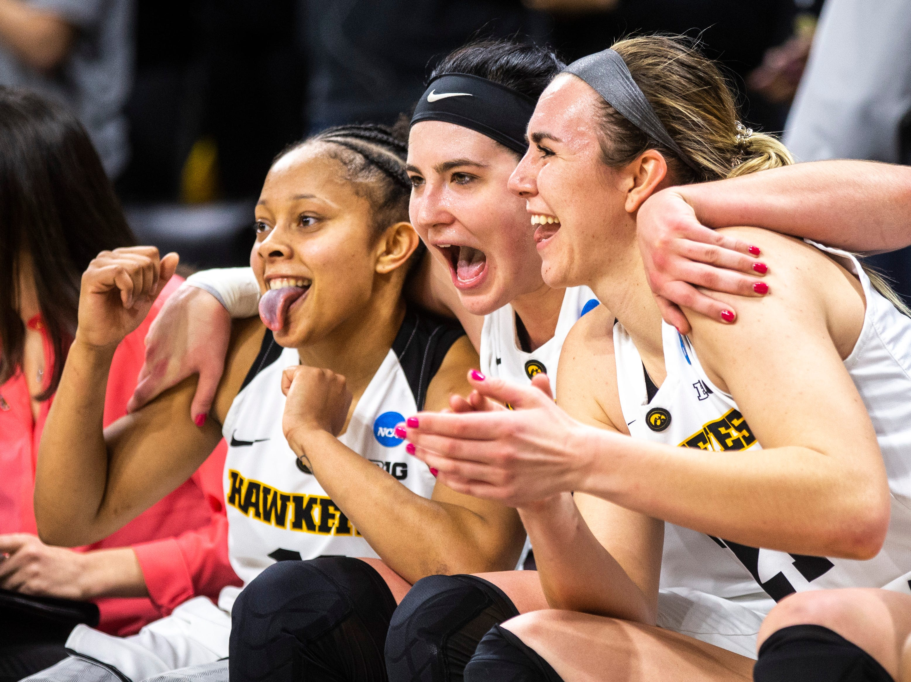 Iowa guard Tania Davis, center Megan Gustafson and forward Hannah Stewart celebrate on the bench during a NCAA women's basketball tournament second-round game, Sunday, March 24, 2019, at Carver-Hawkeye Arena in Iowa City, Iowa.