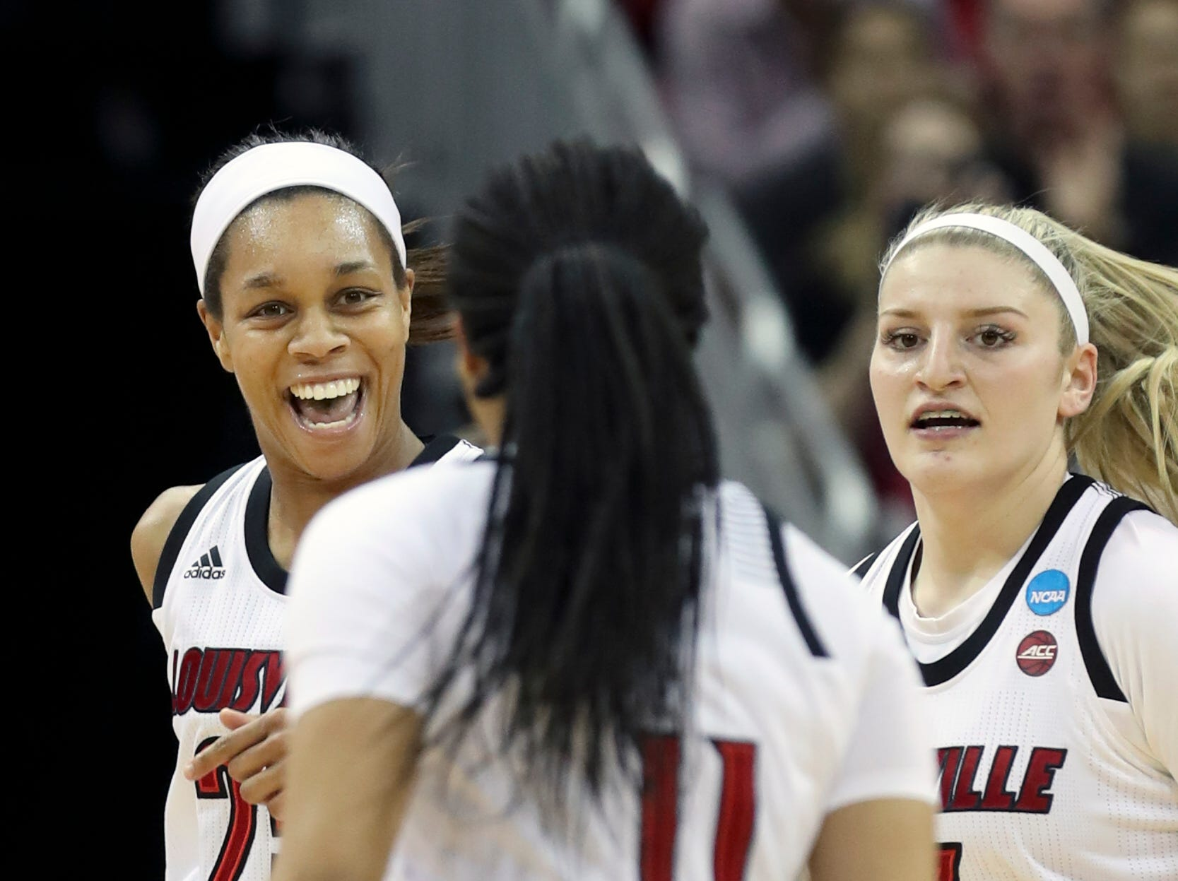 Louisville's Asia Durr, left, Sam Fuehring, right and Arica Carter celebrate after Michigan calls a timeout at the KFC Yum Center on March 24.