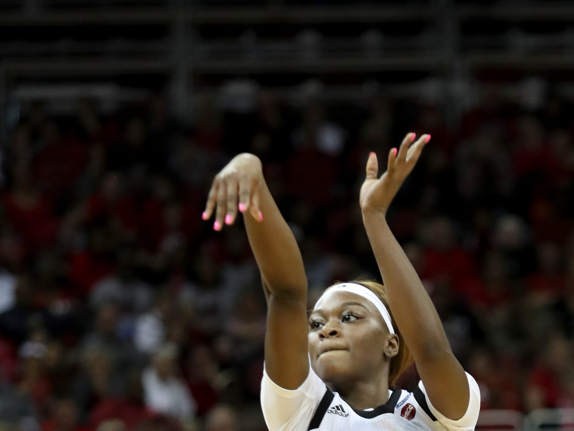 Louisville's Dana Evans knocks down a three against Michigan at the KFC Yum Center on March 24.