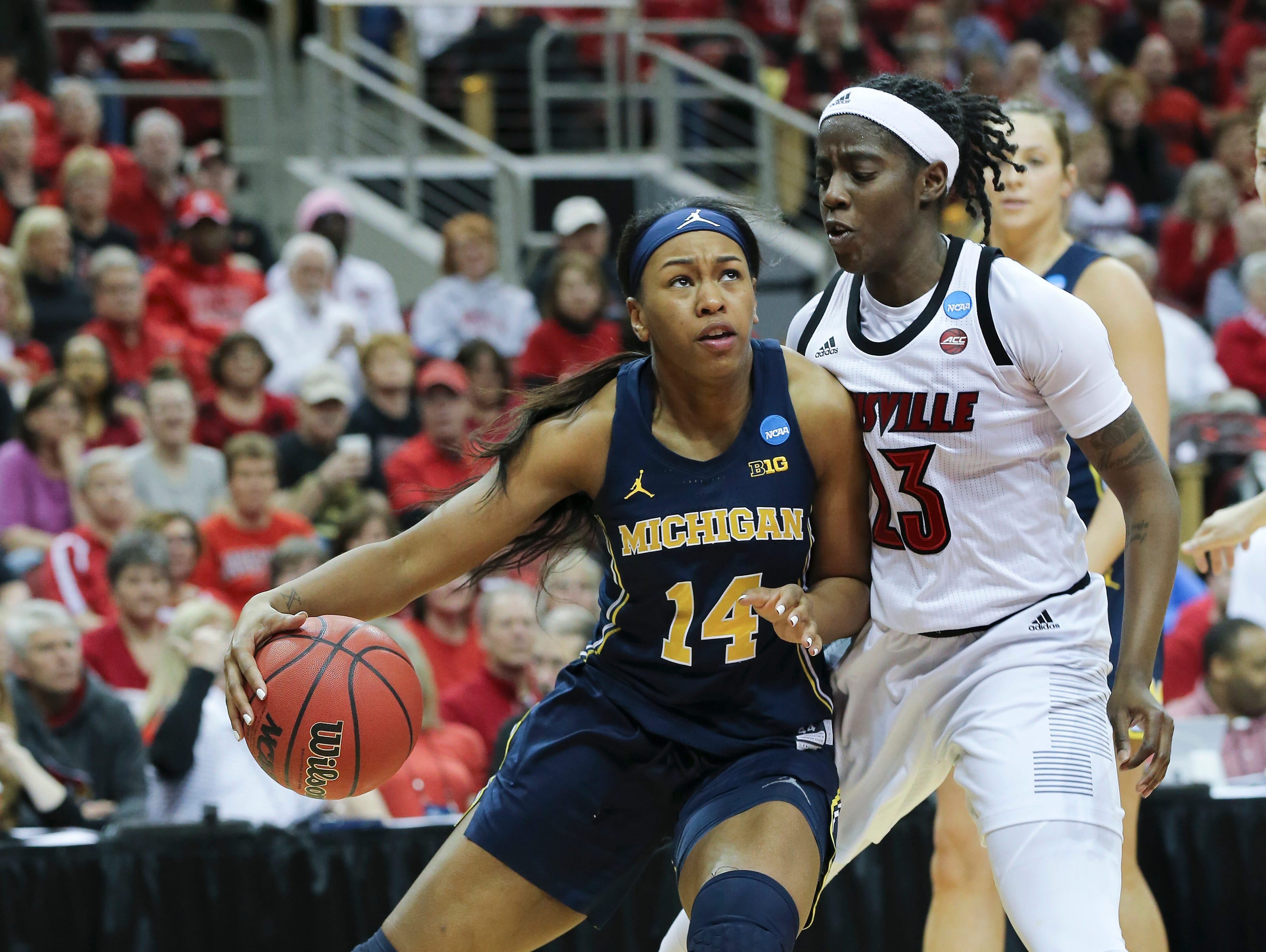 Michigan's Akienreh Johnson (14) drove against U of L's Jazmine Jones (23) during the second round of their NCAA Tournament game at the Yum Center.Mar. 24, 2019