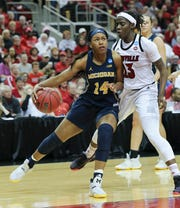 Michigan's Akienreh Johnson (14) drives against Louisville's Jazmine Jones (23) during the second round of their NCAA tournament game at the Yum Center on March 24, 2019.