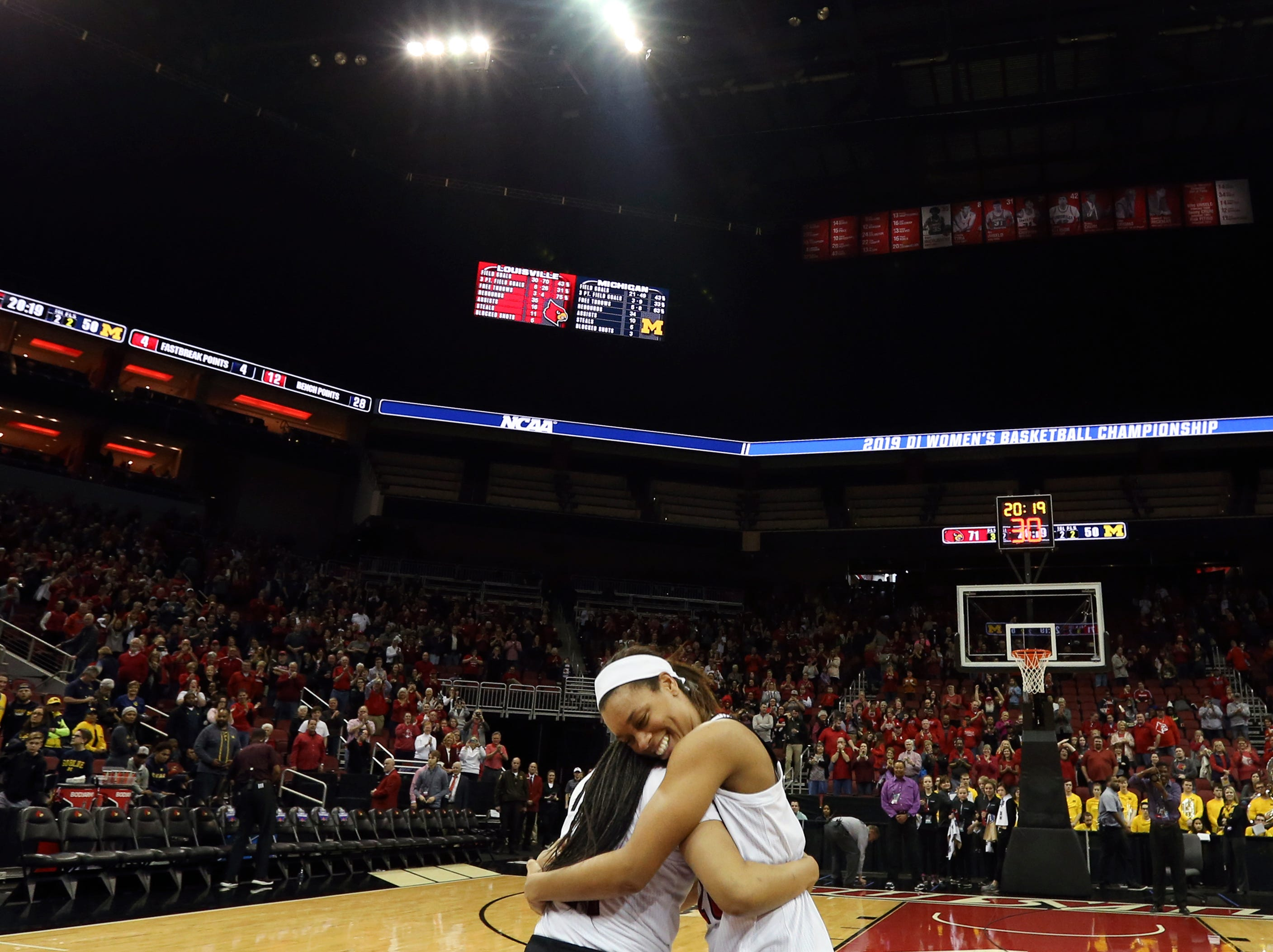 Louisville's Asia Durr  and Arica Carter hug near center court after the Cardinals punch their ticket to the Sweet 16 by beating Michigan at the KFC Yum Center on March 24.