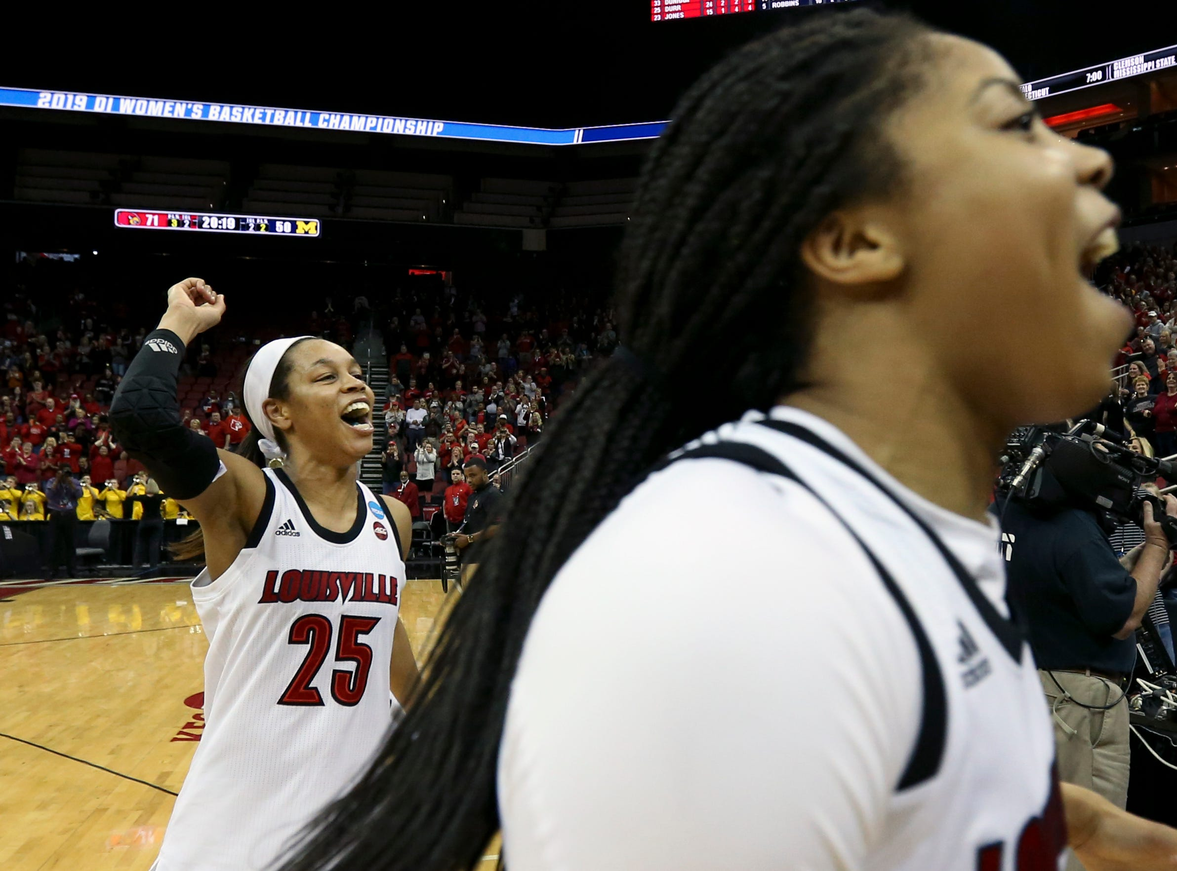 Louisville's Asia Durr , left, and Arica Carter do a celebration lap after the Cardinals punch their ticket to the Sweet 16 by beating Michigan at the KFC Yum Center on March 24.