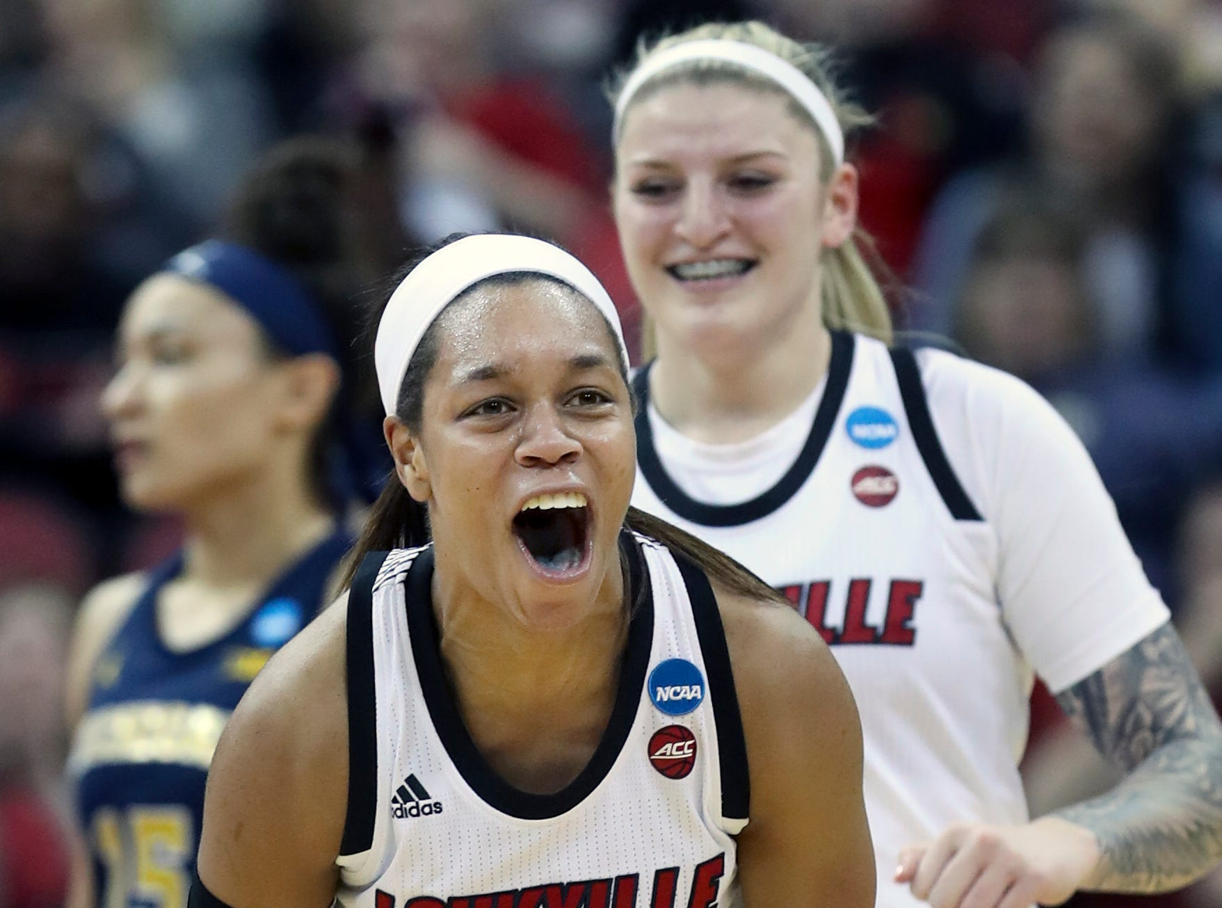 Louisville's Asia Durr celebrates after knocking down a three and drawing the foul against Michigan at the KFC Yum Center on March 24.