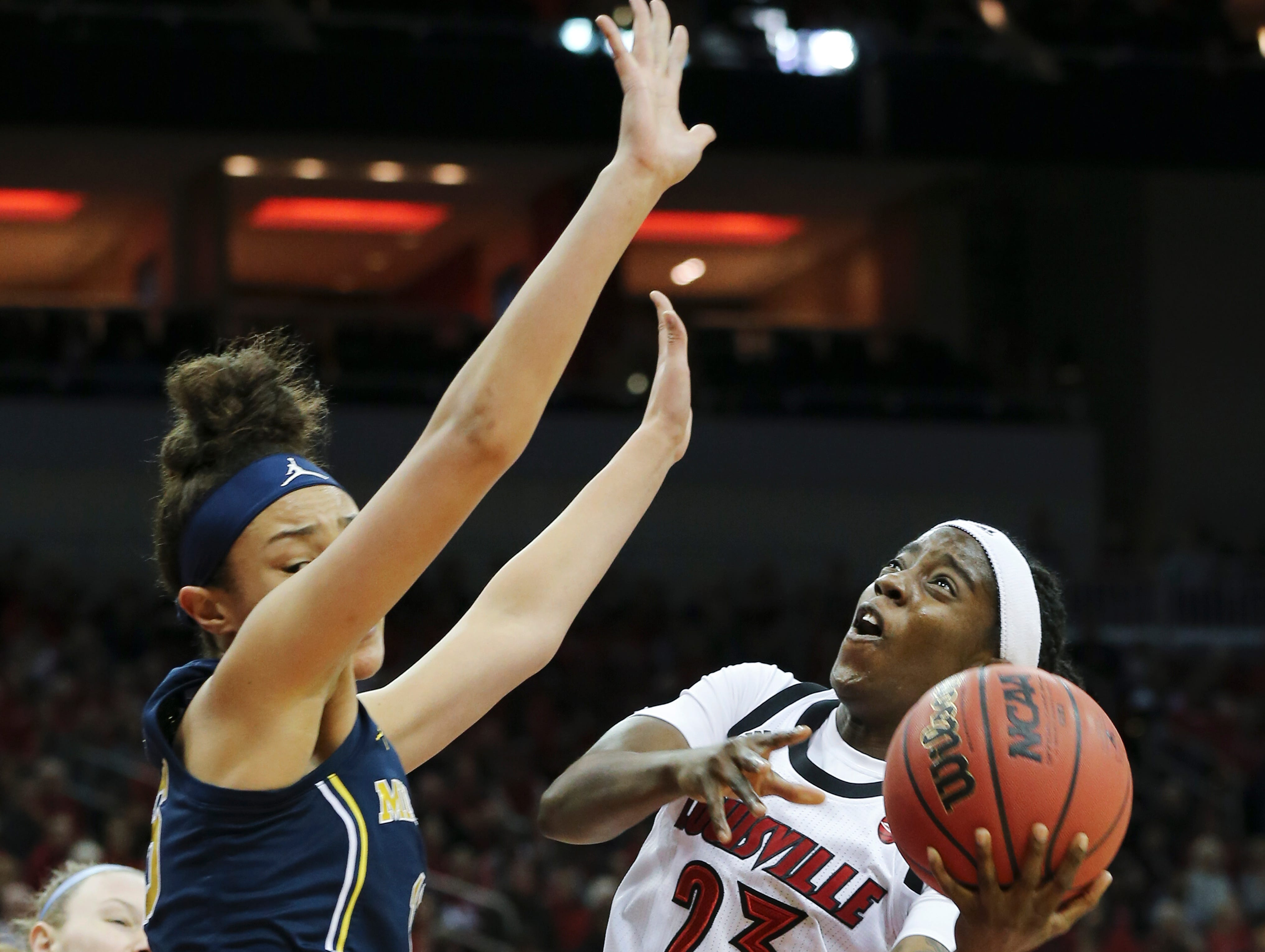 U of L's Jazmine Jones (23) tries to maneuver a tough shot against Michigan's Hailey Brown (15) during the second round of their NCAA Tournament game at the Yum Center.Mar. 24, 2019