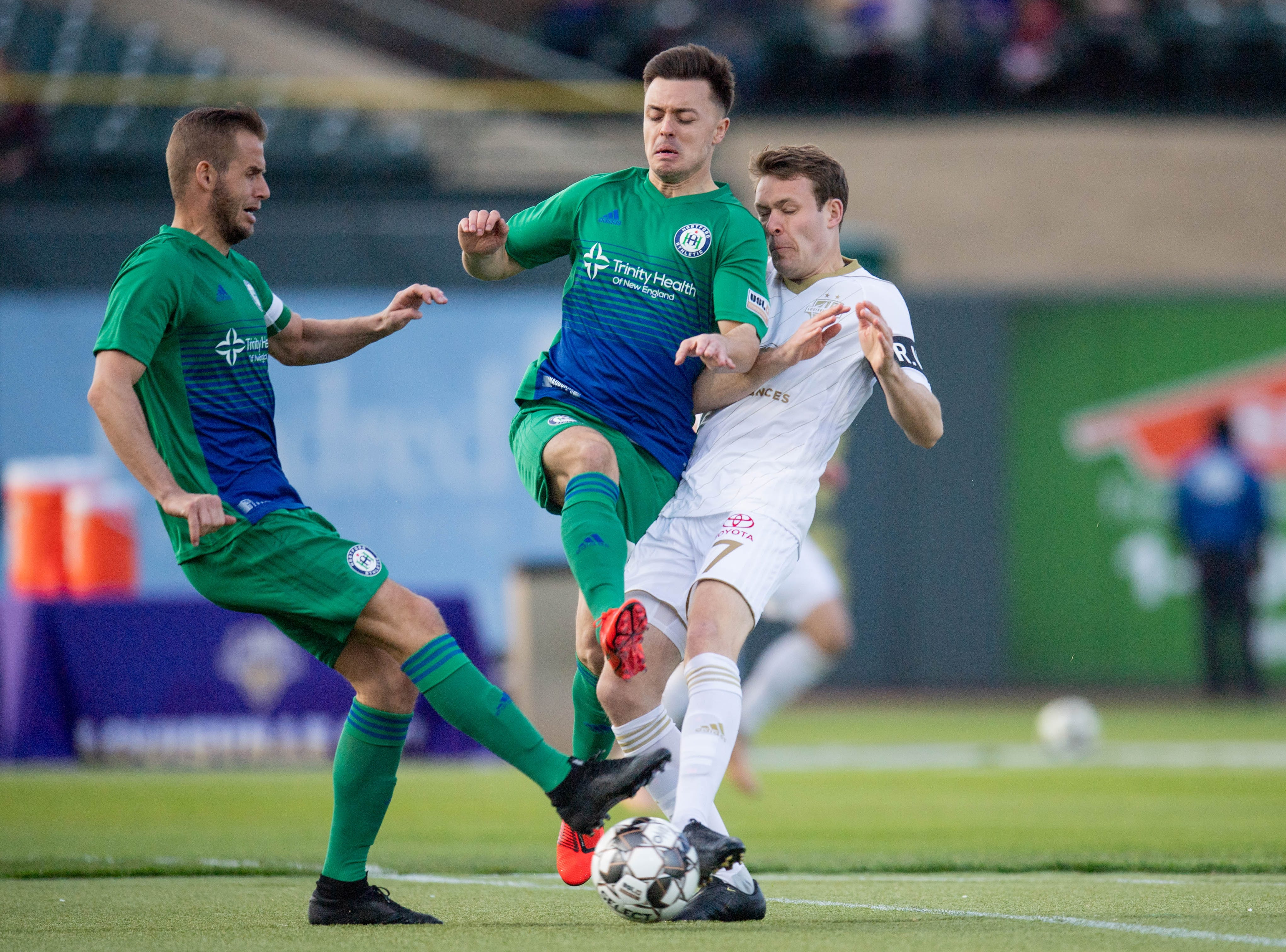 Louisville City FC midfielder Magnus Rasmussen (7) collides with two Hartford Athletic defenders during the season opening match in Louisville, Ky., Saturday, March 23, 2019.