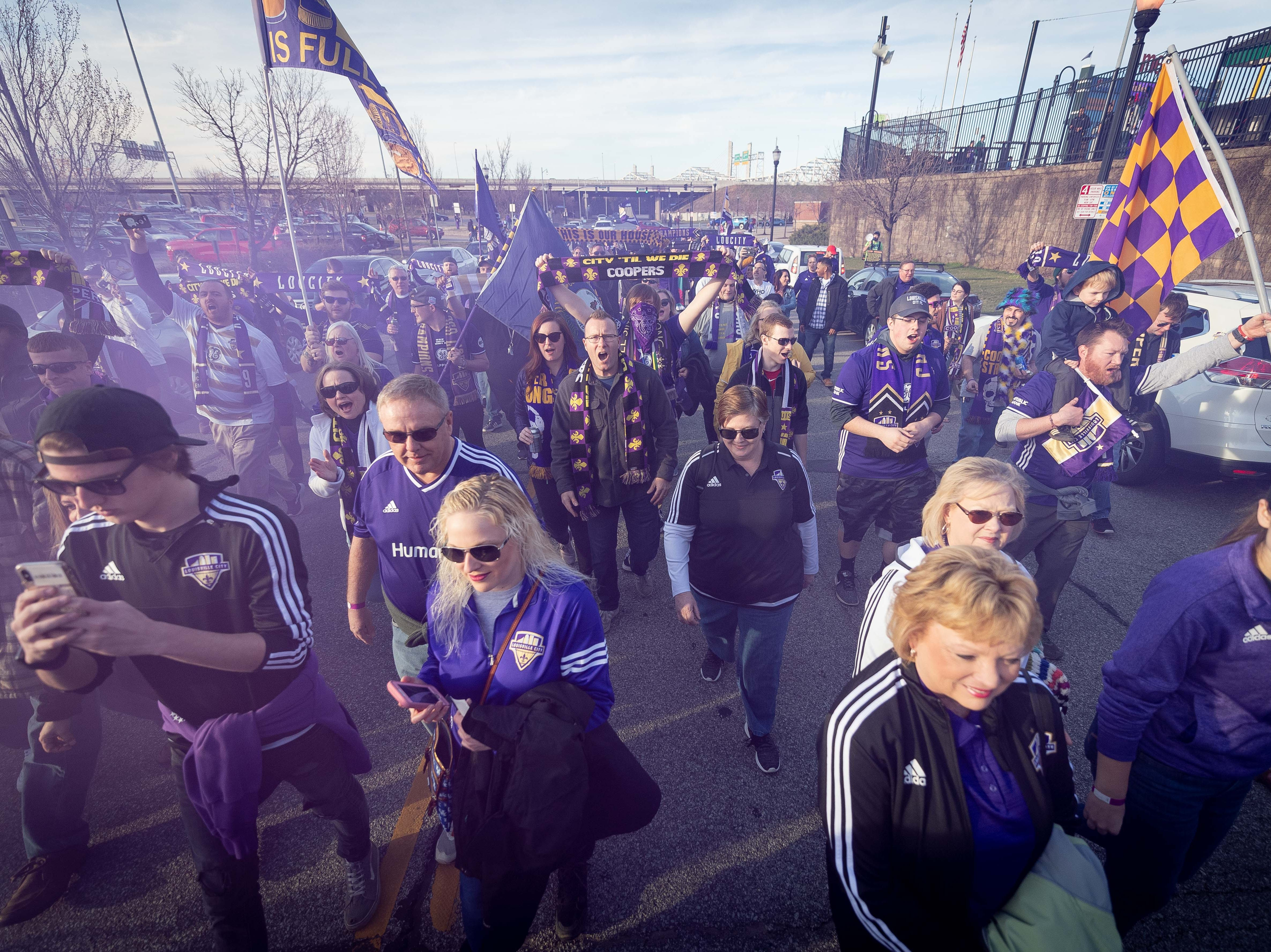 Louisville City FC fans march up Preston Street on their way to the match in Louisville, Ky., Saturday, March 23, 2019.