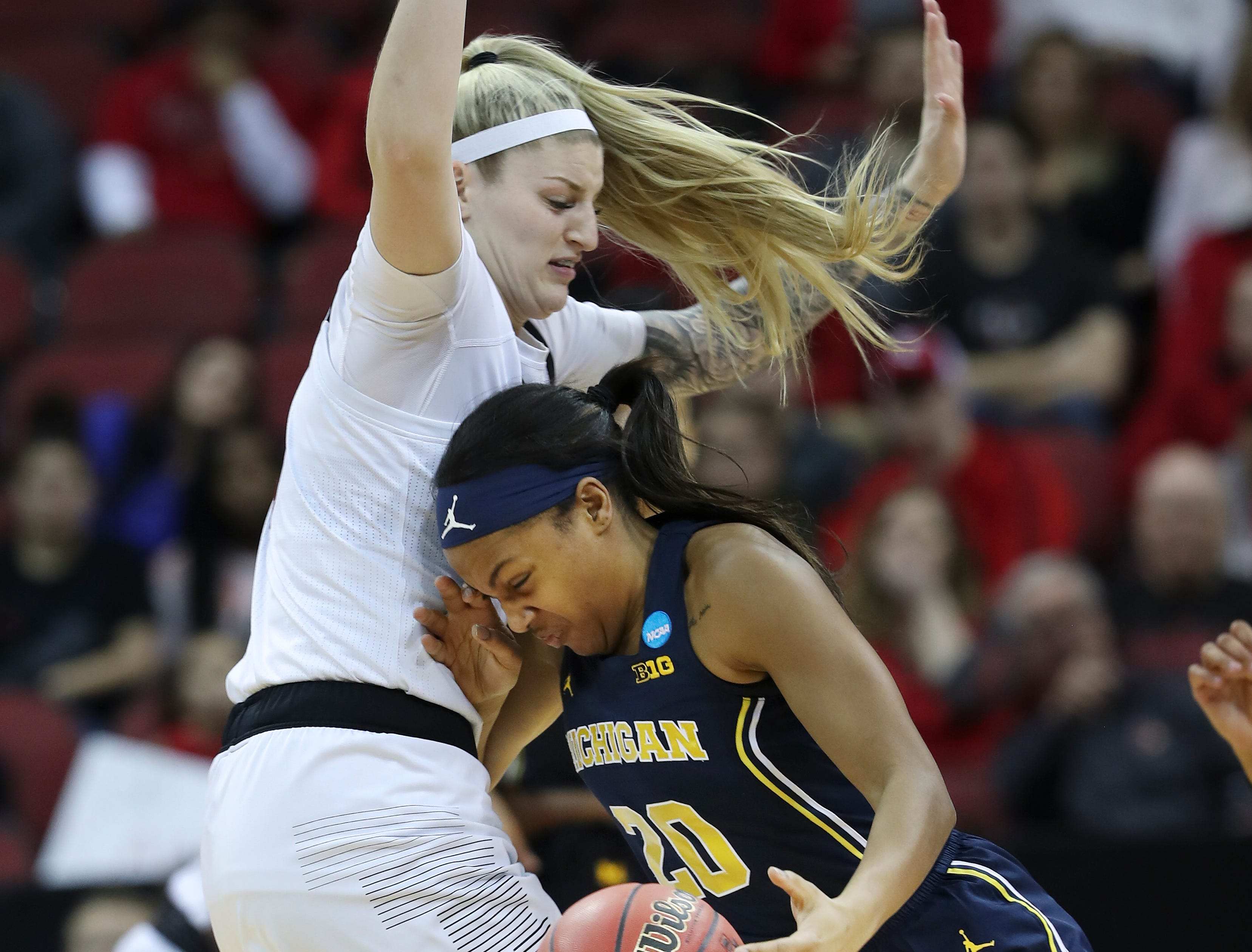 Michigan's Deja Church (20) drives against U of L'sSam Fuehring (3) during the second round of their NCAA Tournament game at the Yum Center.Mar. 24, 2019