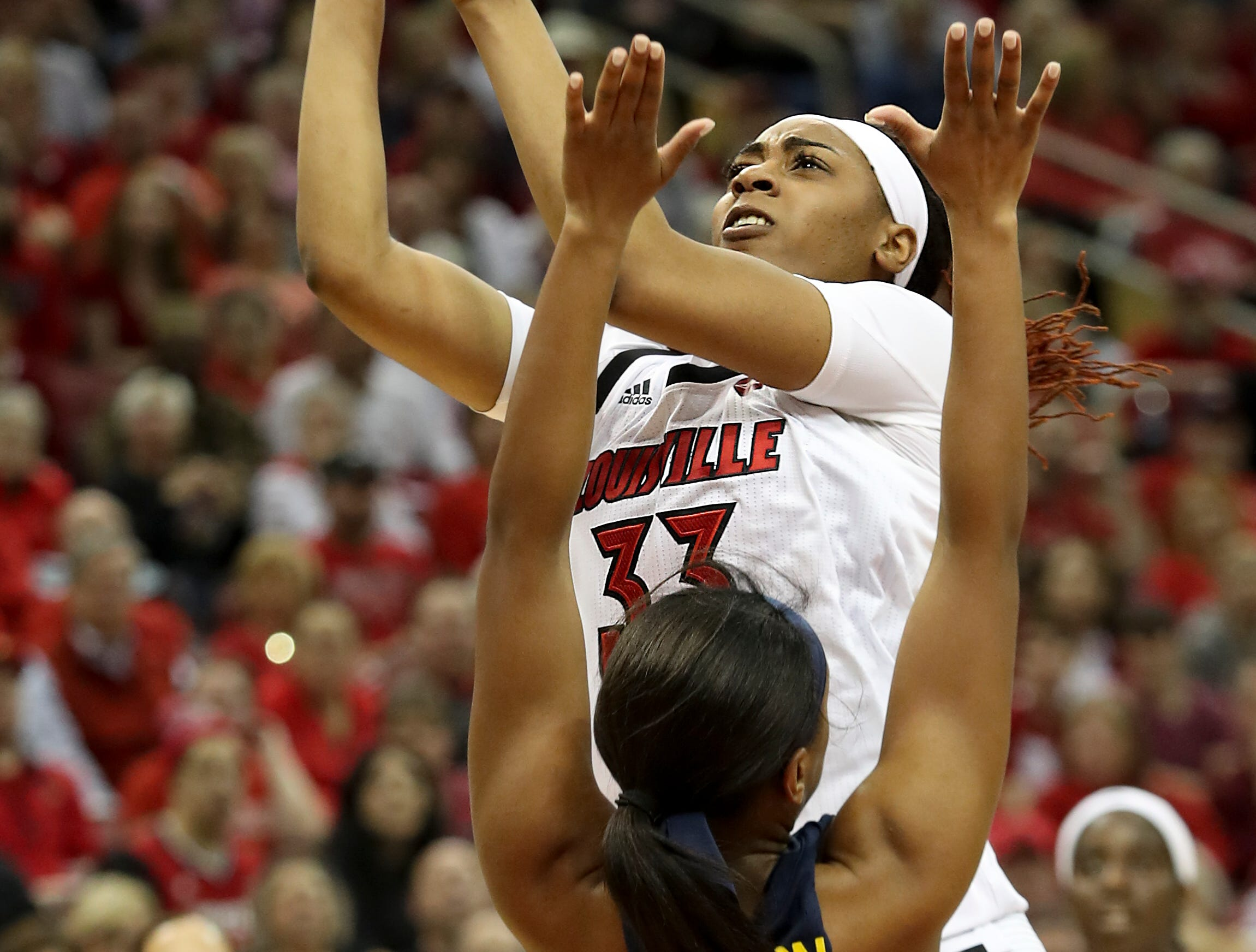 Louisville's Bionca Dunham goes up hard against Michigan's Akienreh Johnson at the KFC Yum Center on March 24.