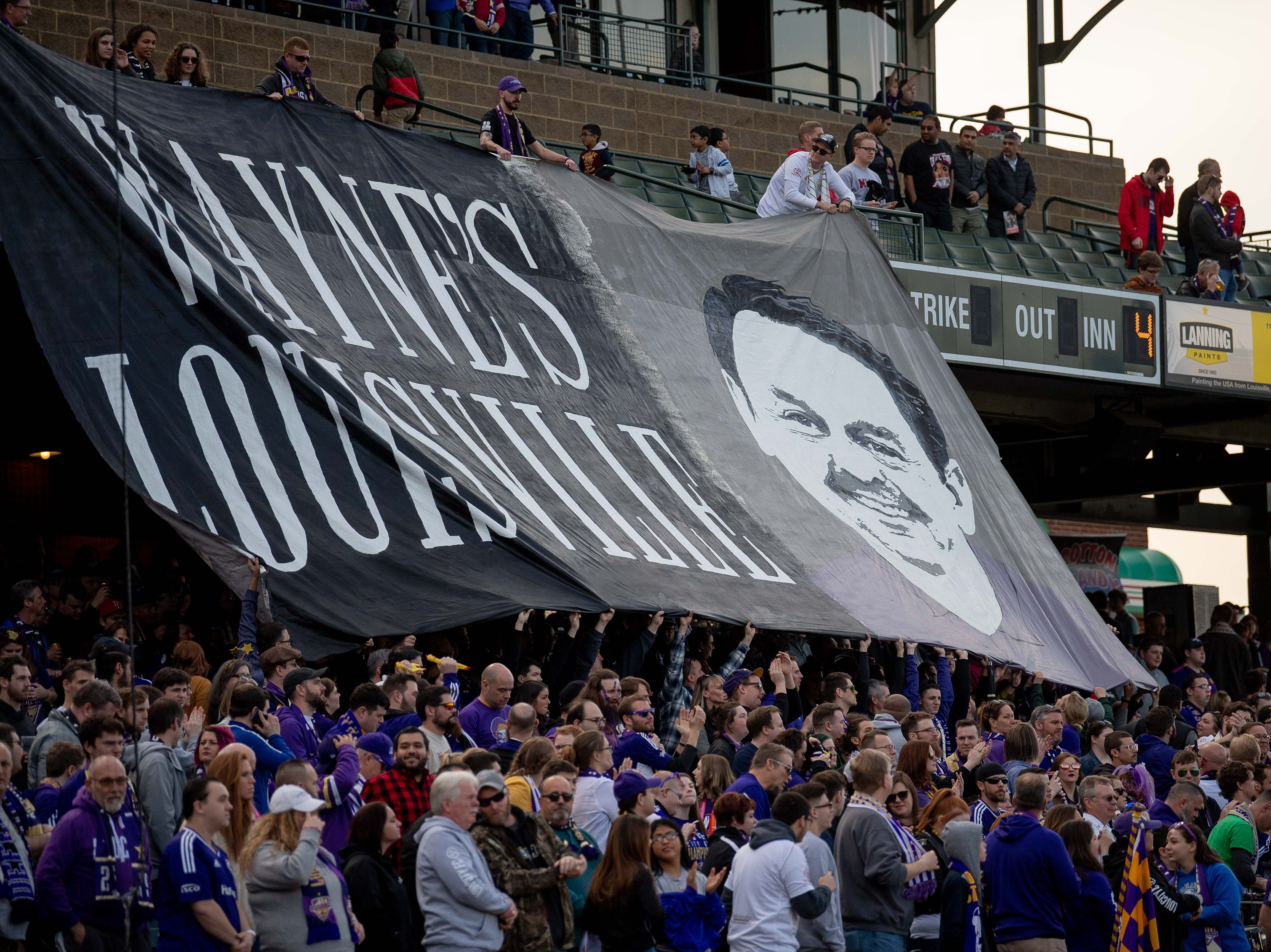 A banner is displayed in memory of Louisville City FC team founder Wayne Estopinal before the season opening match in Louisville, Ky., Saturday, March 23, 2019.