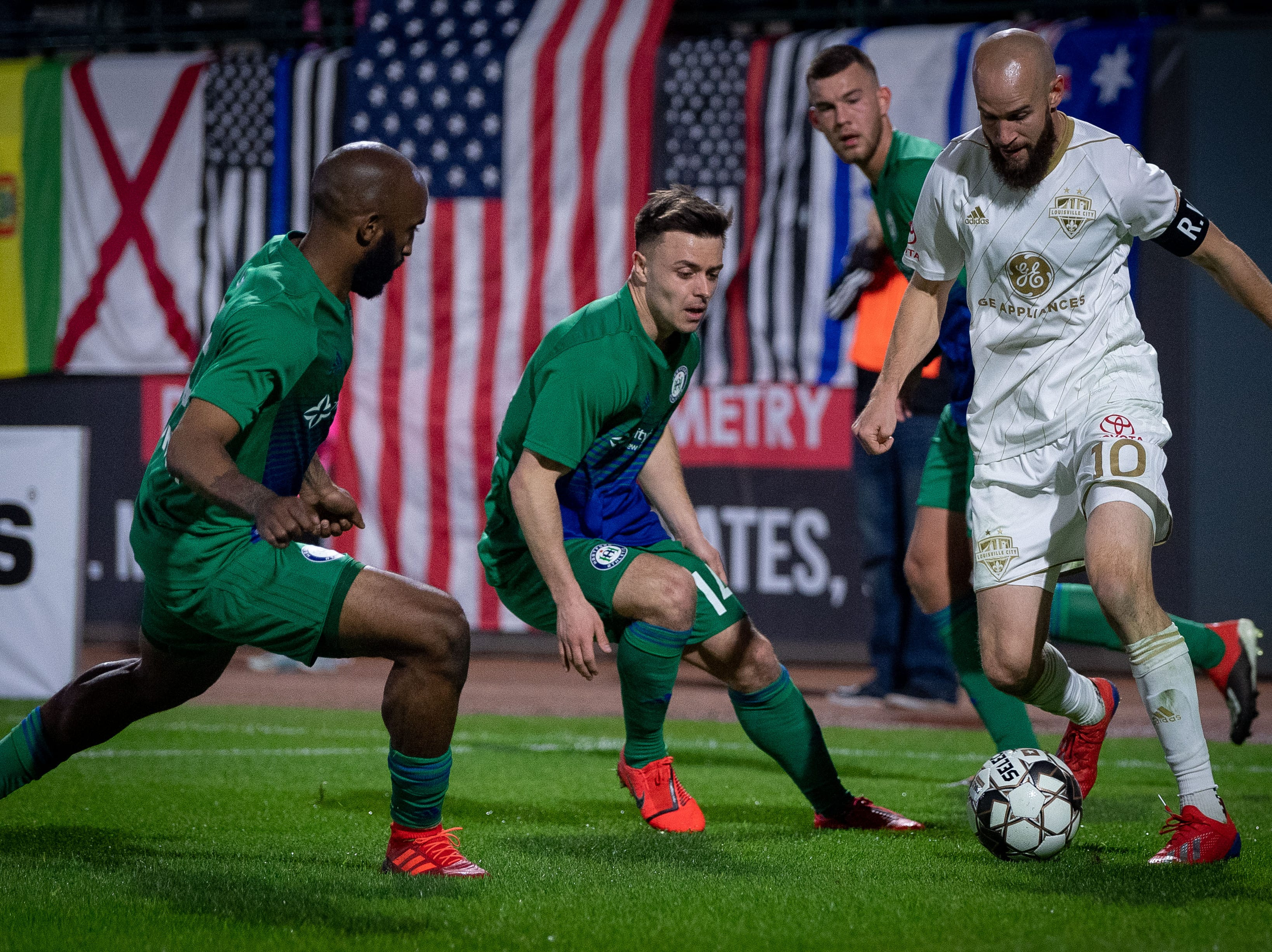 Louisville City FC midfielder Brian Ownby (10) plays against three Hartford Athletic defenders during the season opening match in Louisville, Ky., Saturday, March 23, 2019.