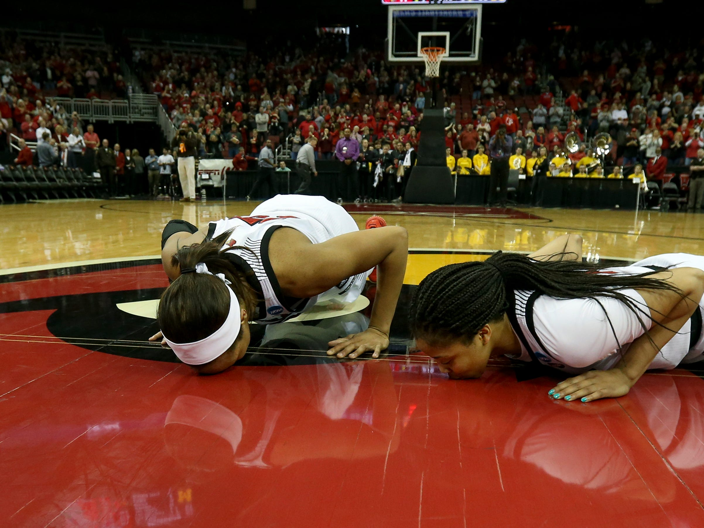 Louisville's Asia Durr , left, and Arica Carter kiss center court after they played their last game as a Cardinal at KFC Yum Center on March 24.