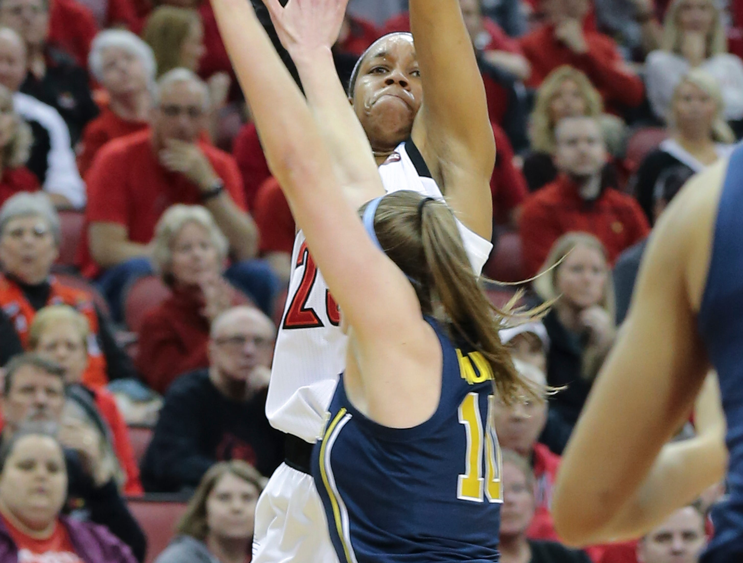 U of L's Asia Durr (25) shoots a three-point shot against against Michigan's Nicole Munger (10) during the second round of their NCAA Tournament game at the Yum Center.Mar. 24, 2019