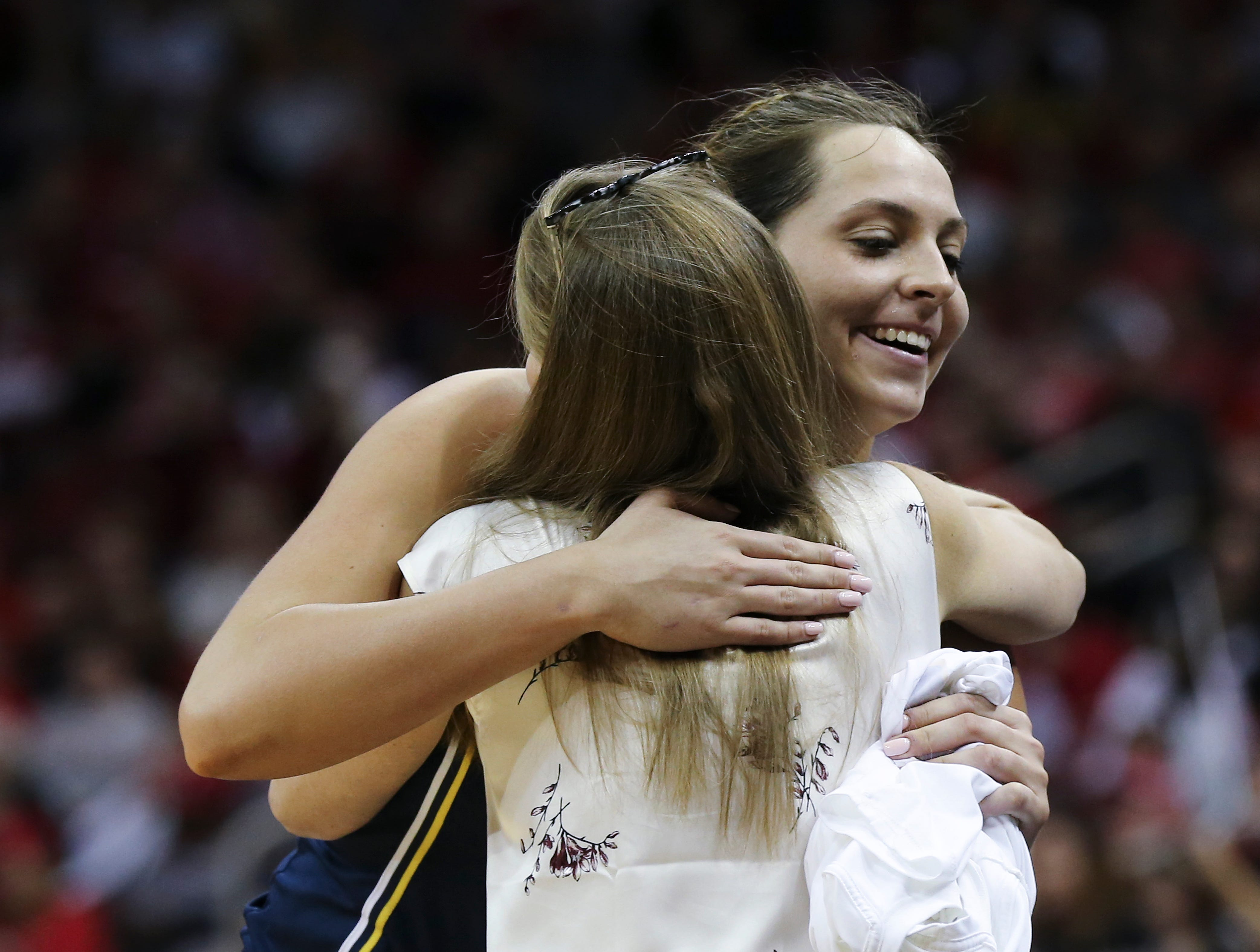 Michigan's Hallie Thome (30) embraced head coach Kim Barnes Arico during the closing minutes of their 71-50 loss to U of L in the second round of their NCAA Tournament game at the Yum Center.  Mar. 24, 2019