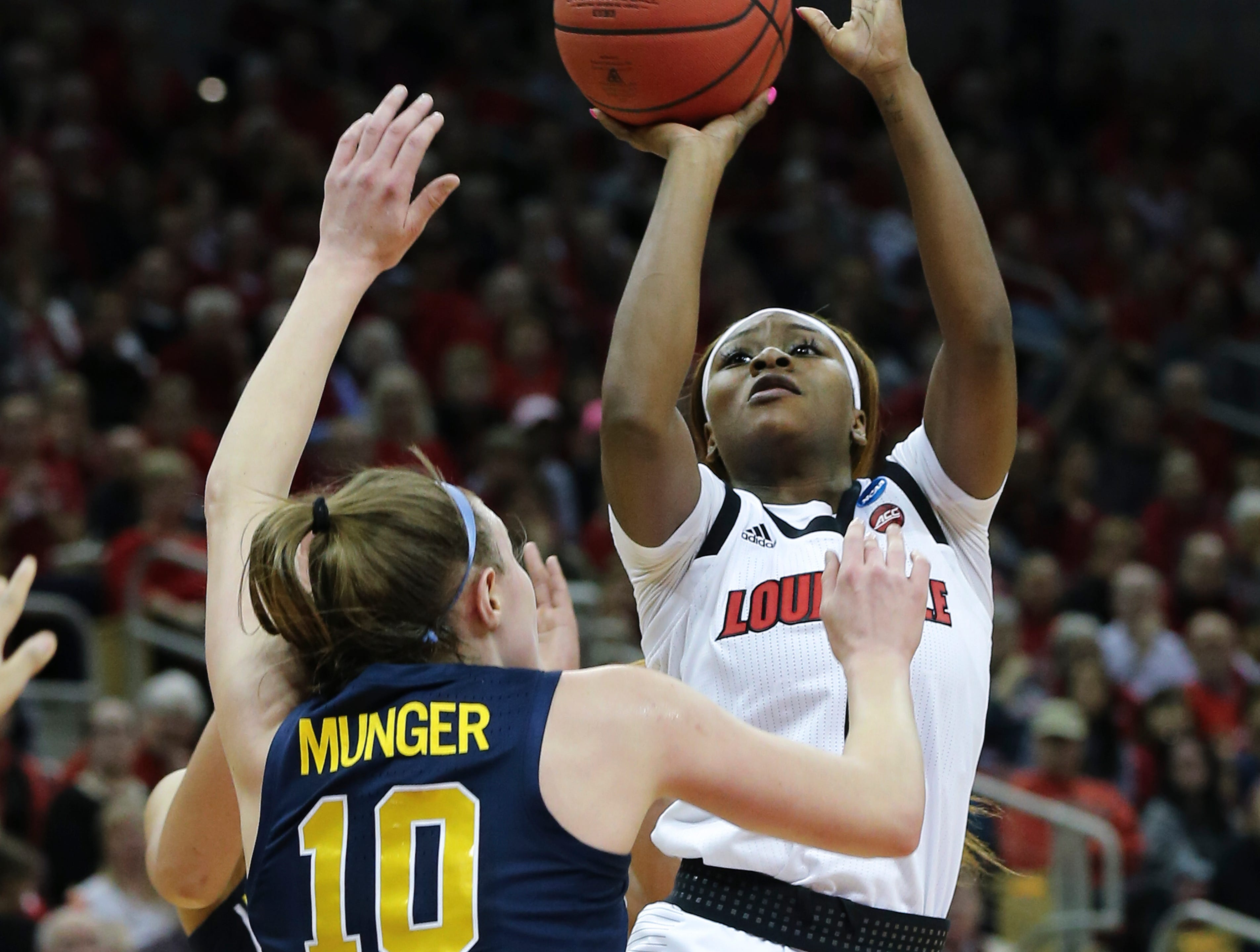 U of L's Dana Evans (1) shoots against Michigan's Nicole Munger (10) during the second round of their NCAA Tournament game at the Yum Center.Mar. 24, 2019