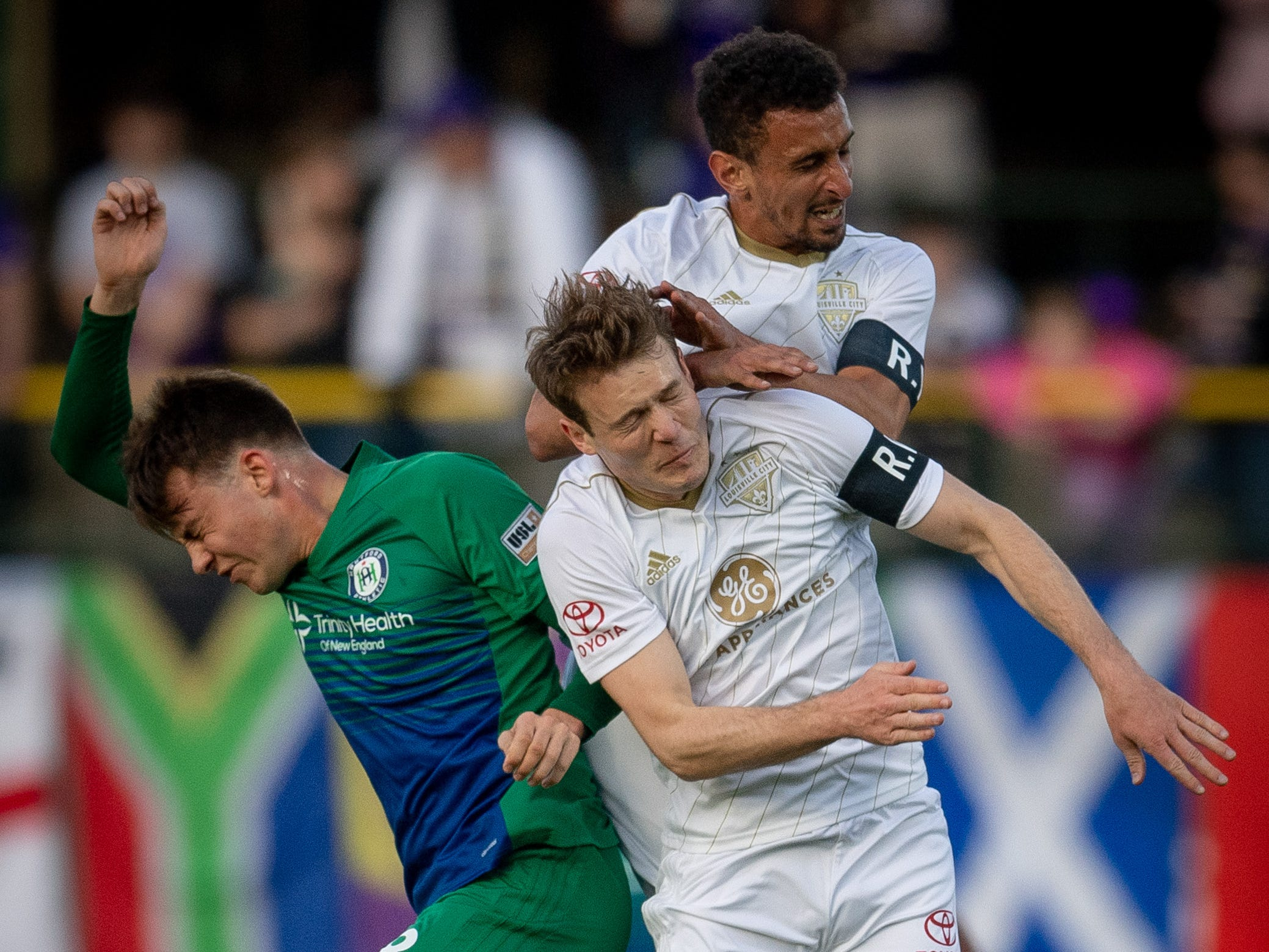 Louisville City FC defender Paco Craig (5) and defender Magnus Rasmussen (7) collide with Hartford Athletic Mads Jorgensen during the season opening match in Louisville, Ky., Saturday, March 23, 2019.
