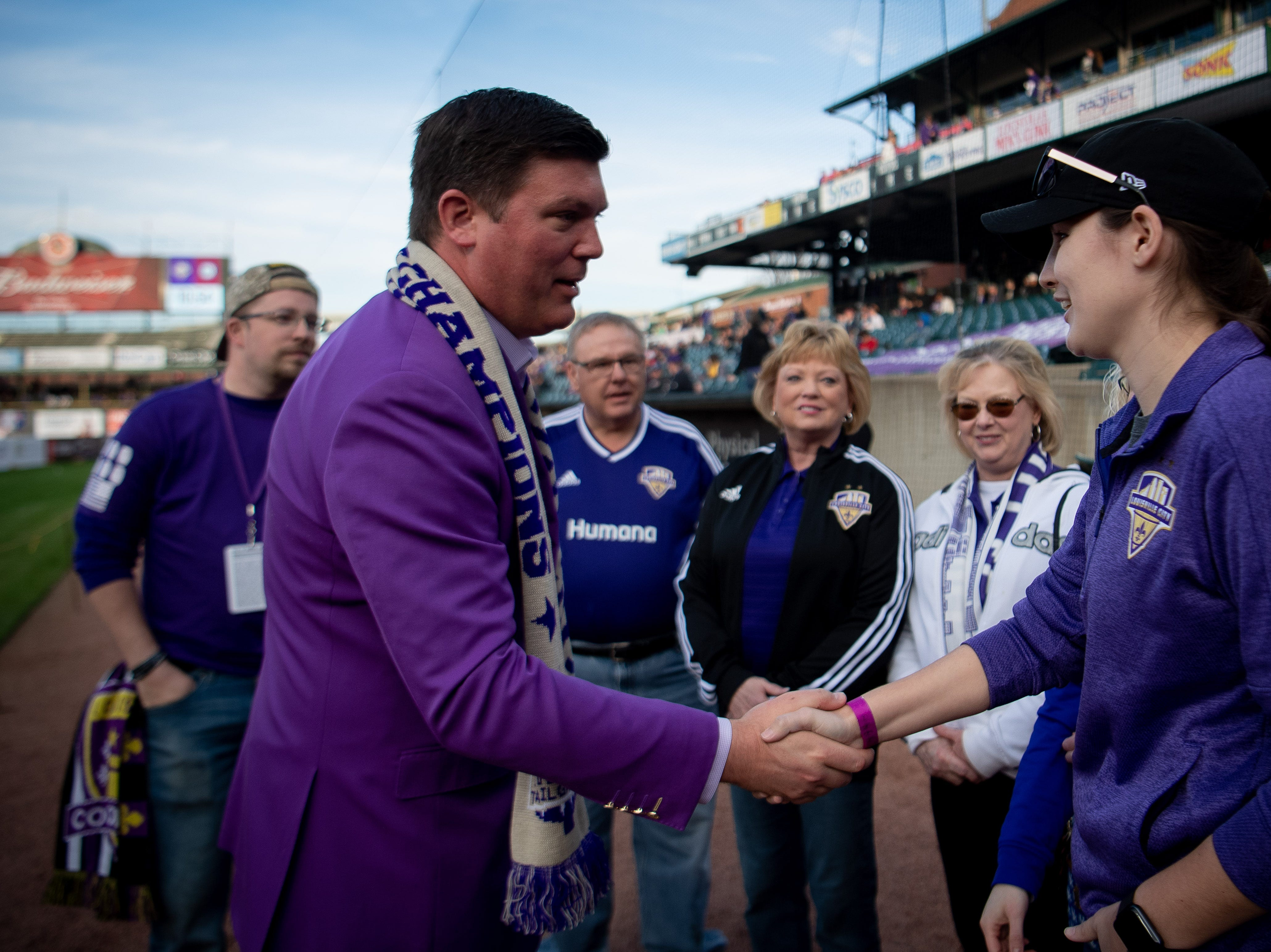 Louisville City FC president Brad Estes greets the family of Wayne Estopinal before the season opening match in Louisville, Ky., Saturday, March 23, 2019.