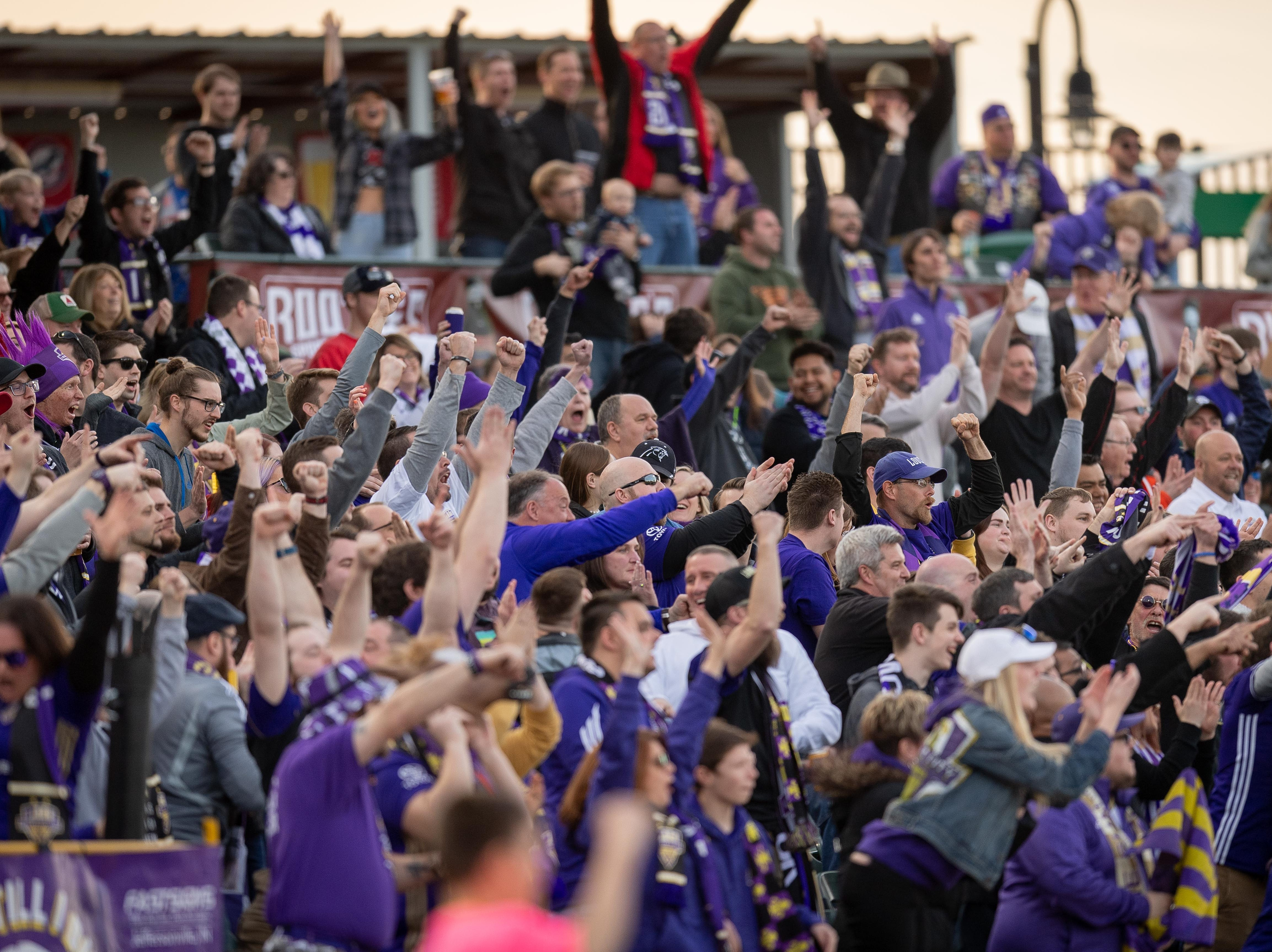Louisville City FC fans celebrate after a goal during the season opening match in Louisville, Ky., Saturday, March 23, 2019.