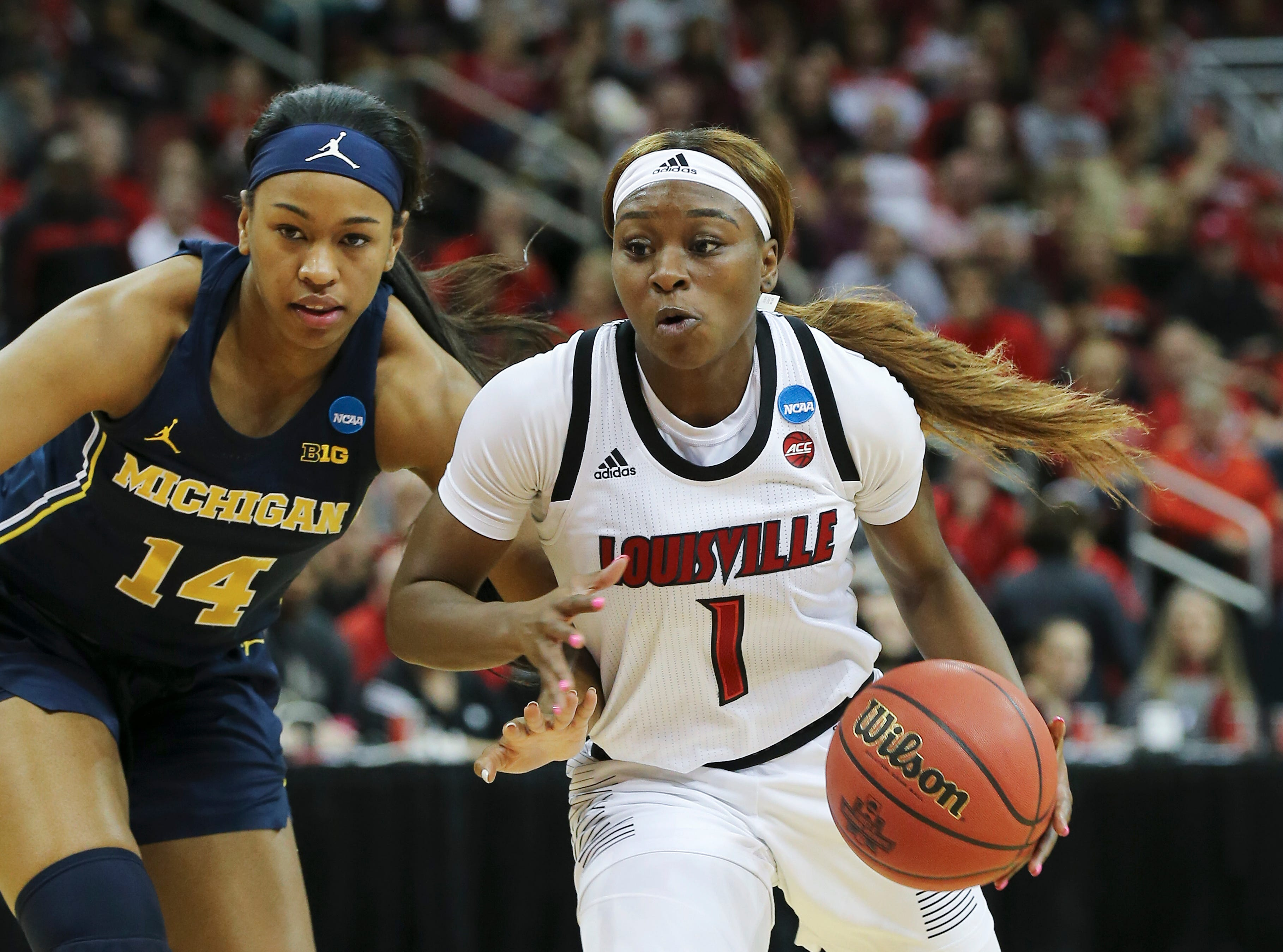 U of L's Dana Evans (1) drove against Michigan's Akienreh Johnson (14) in the second round of their NCAA Tournament game at the Yum Center.  Mar. 24, 2019