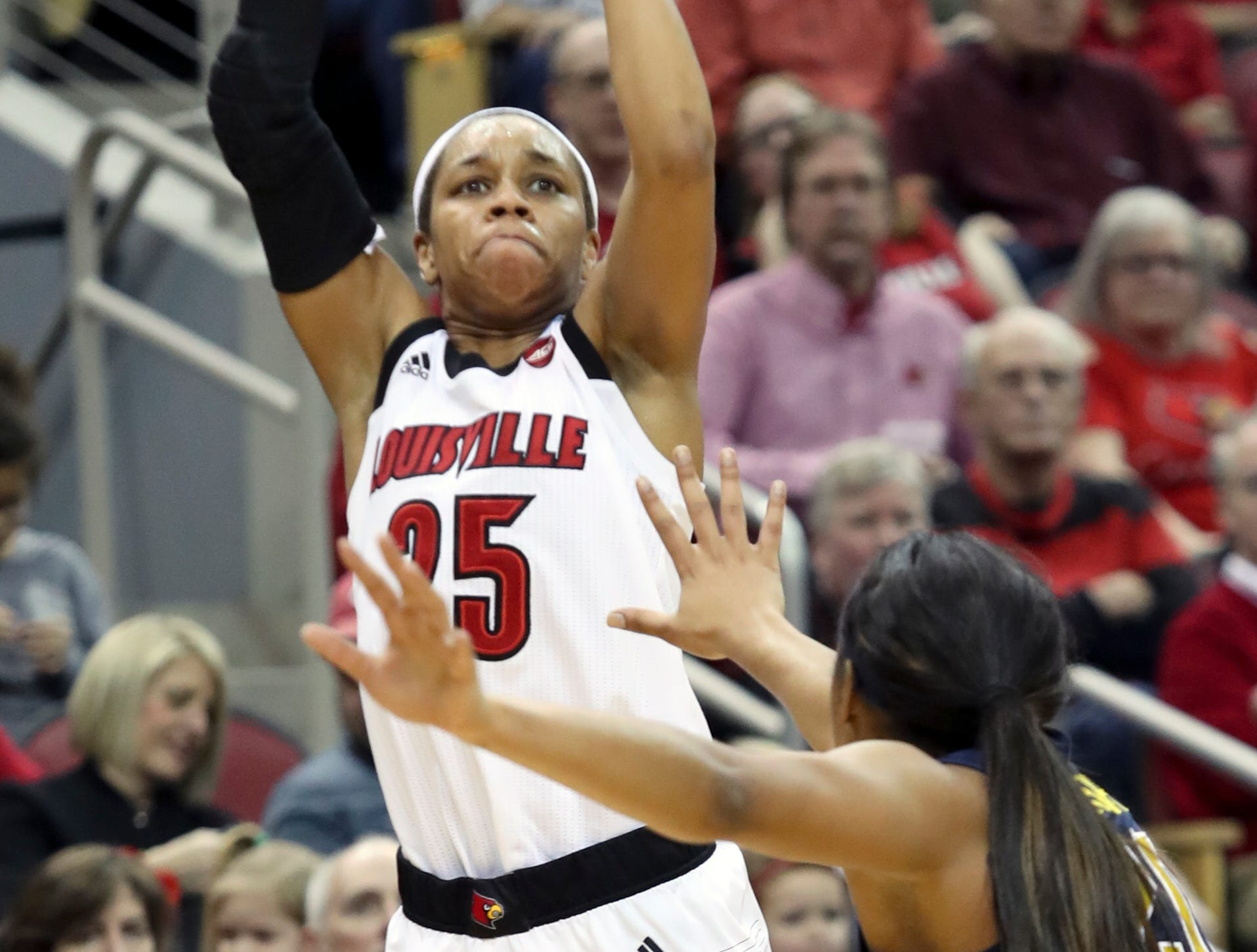 Louisville's Asia Durr knocks down a shot over Michigan's Deja Church at the KFC Yum Center on March 24.