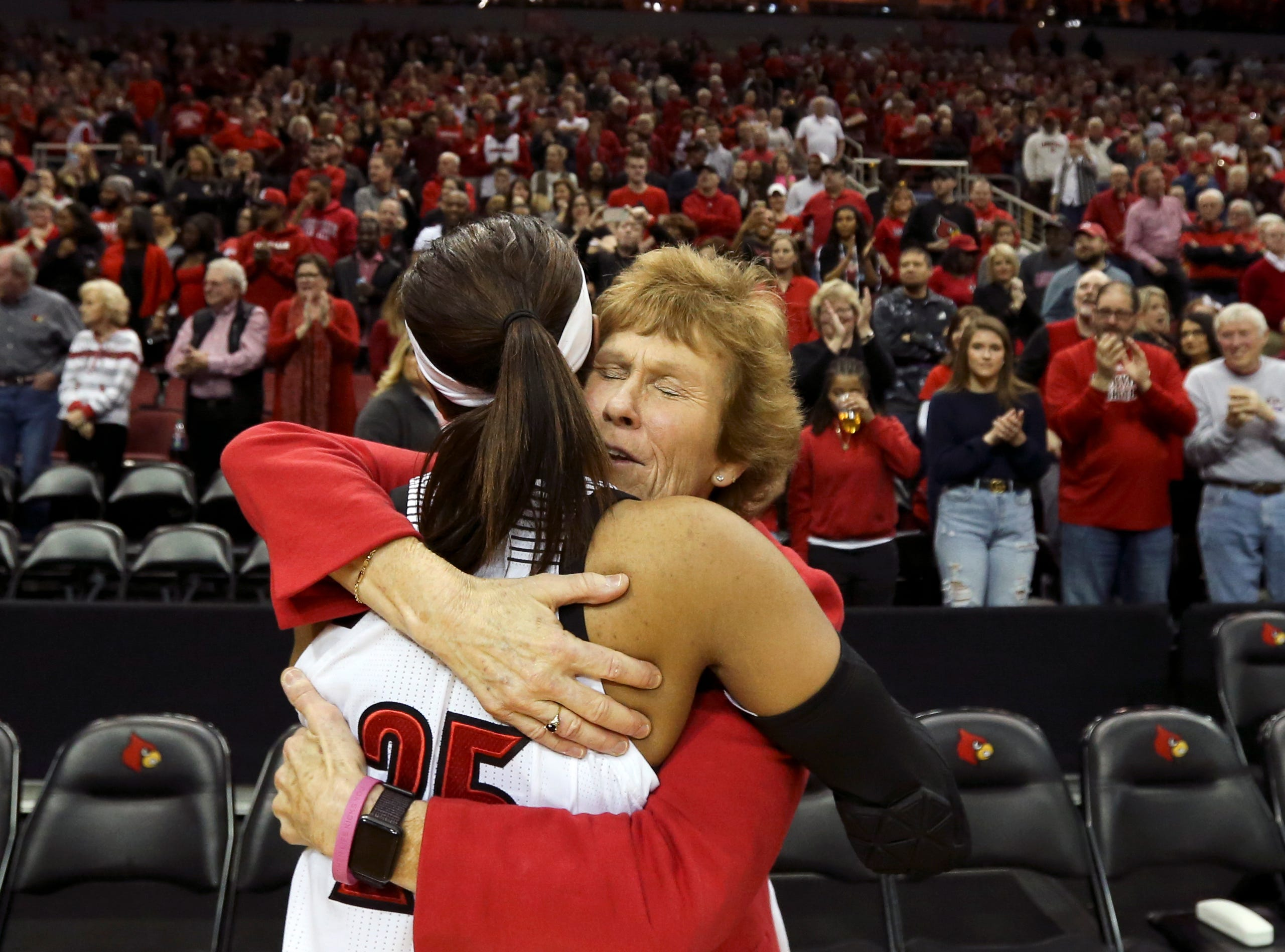 Louisville's Asia Durr  hugs Beth Burns, associate strength and conditioning coach, after the Cardinals punch their ticket to the Sweet 16 by beating Michigan at the KFC Yum Center on March 24.