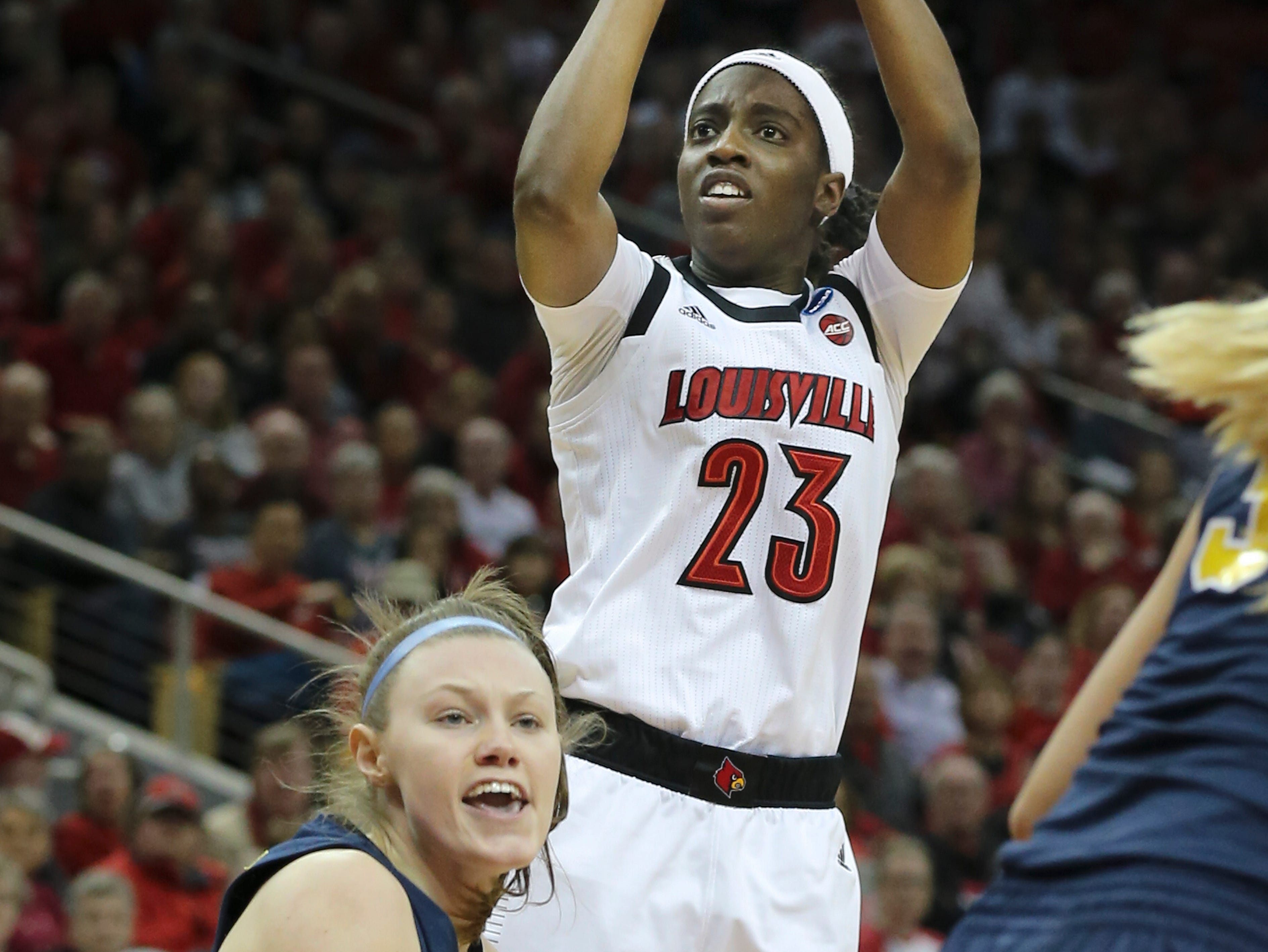 U of L's Jazmine Jones (23) fired up a jumper against the Michigan defense during the second round of their NCAA Tournament game at the Yum Center.Mar. 24, 2019