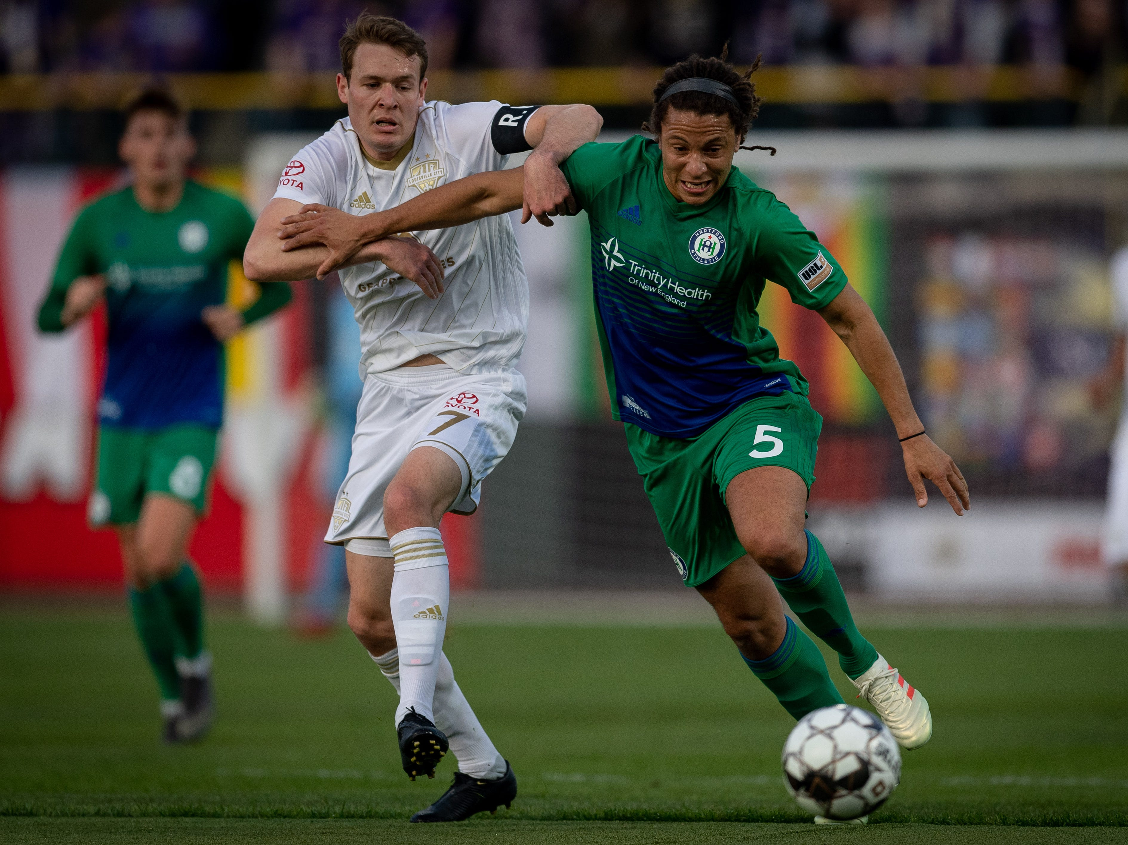 Louisville City FC midfielder Magnus Rasmussen (7) plays against Hartford Athletic Tyler David during the season opening match in Louisville, Ky., Saturday, March 23, 2019.