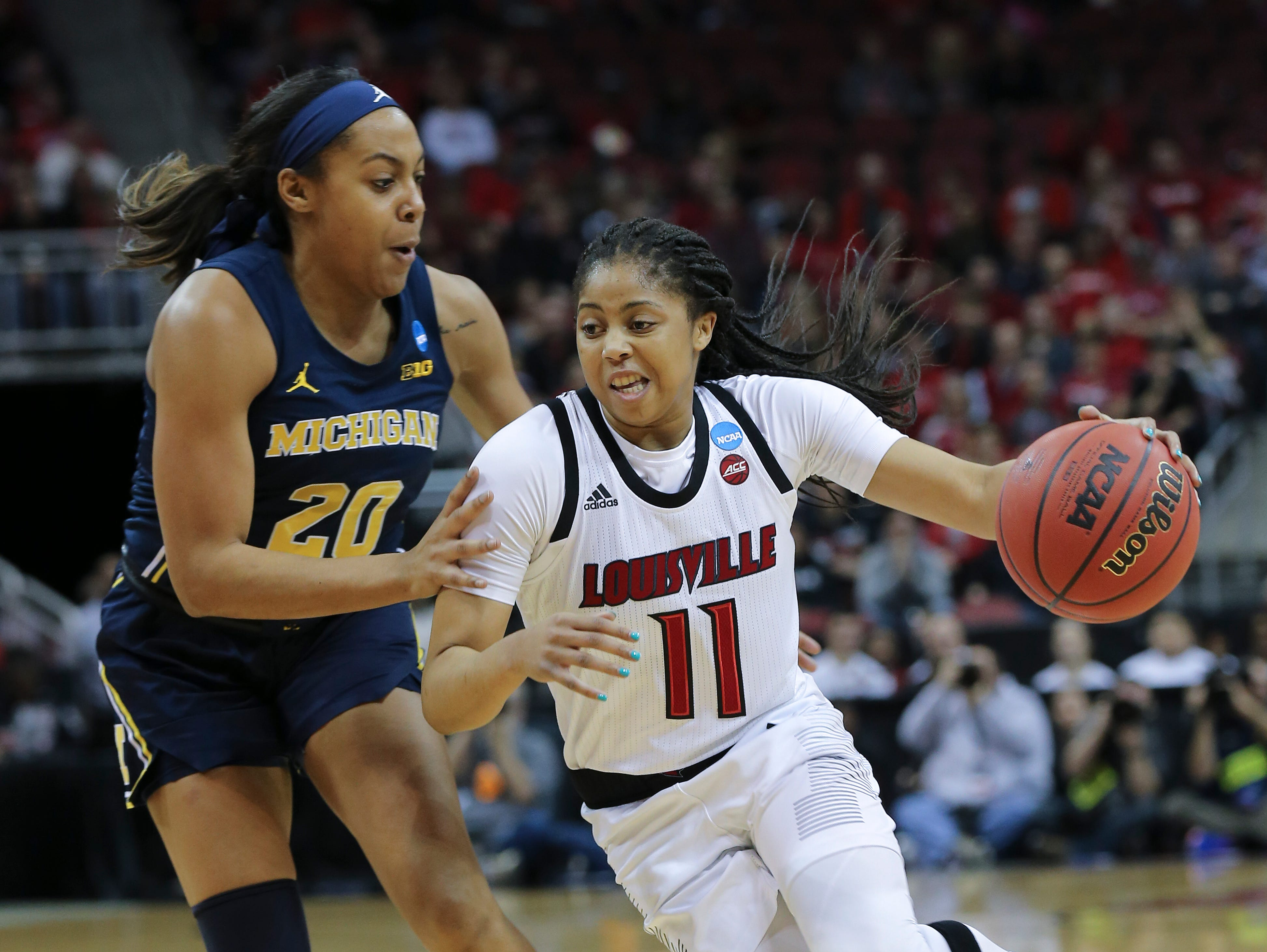 U of L's Arica Carter (11) drove against Michigan's Deja Church (20) in the second round of their NCAA Tournament game at the Yum Center.  Mar. 24, 2019