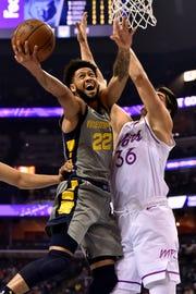 Memphis Grizzlies guard Tyler Dorsey (22) shoots against Minnesota Timberwolves forward Dario Saric (36) in the first half of an NBA basketball game Saturday, March 23, 2019, in Memphis, Tenn. (AP Photo/Brandon Dill)