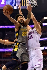 Memphis Grizzlies guard Tyler Dorsey (22) shoots against Minnesota Timberwolves forward Dario Saric (36) in the first half of an NBA basketball game Saturday, March 23, 2019, in Memphis, Tenn. (AP Photo/Brandon Dill)