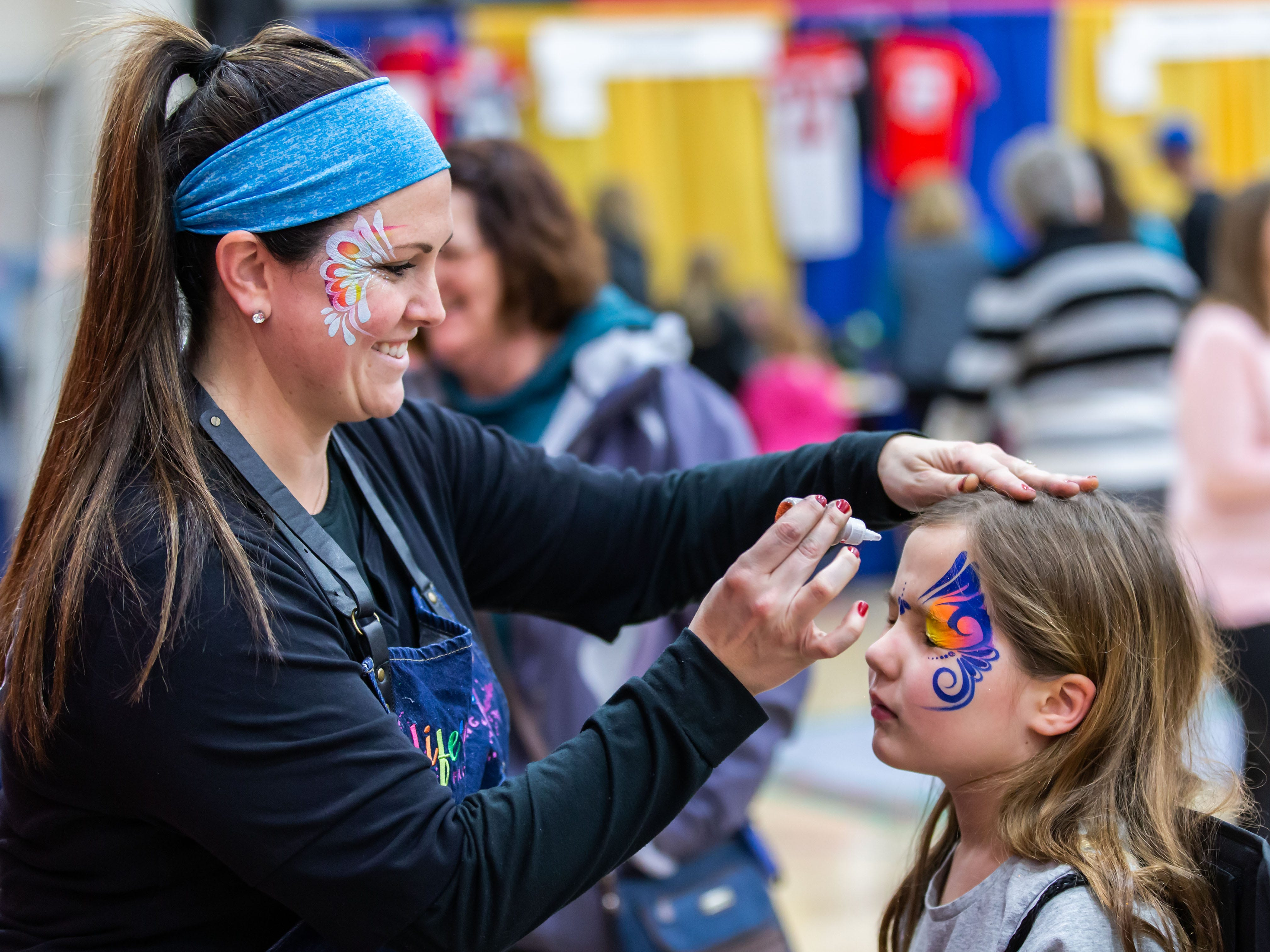 Seven-year-old Nora Booth of Nashotah sits for a face painting by artist Leea Woolard of Life's a Party - Face Painting, during Lake Country Community Fest at Arrowhead High School in Hartland on Saturday, March 23, 2019. The event featured 140 exhibitor booths, a food court, live demonstrations, children's activities, entertainment, healthcare clinics and more.