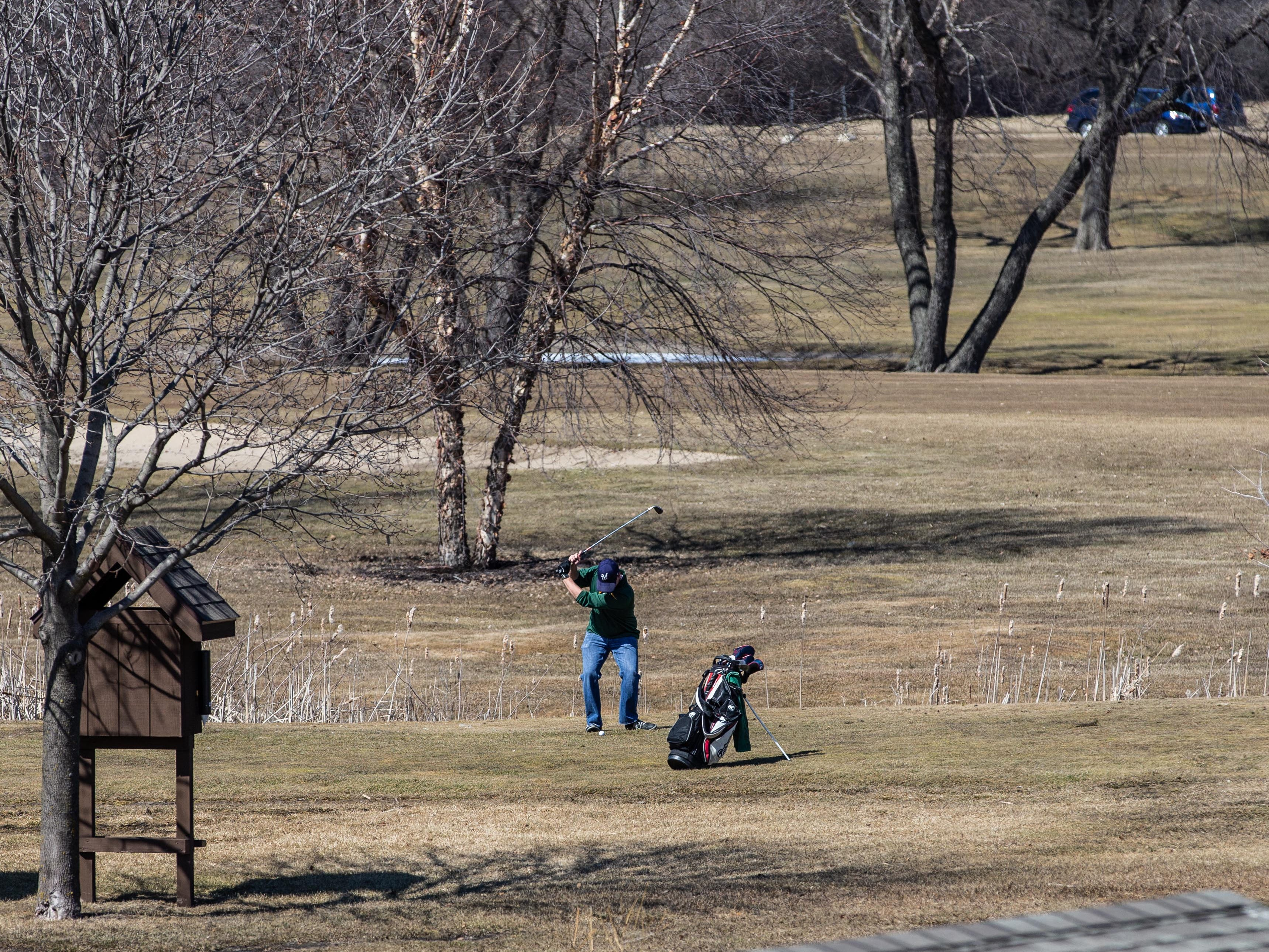 A golfer plays through at Moor Downs Golf Course in Waukesha on Saturday, March 23, 2019. Warm sunny weather lured many enthusiasts outside to enjoy the game.