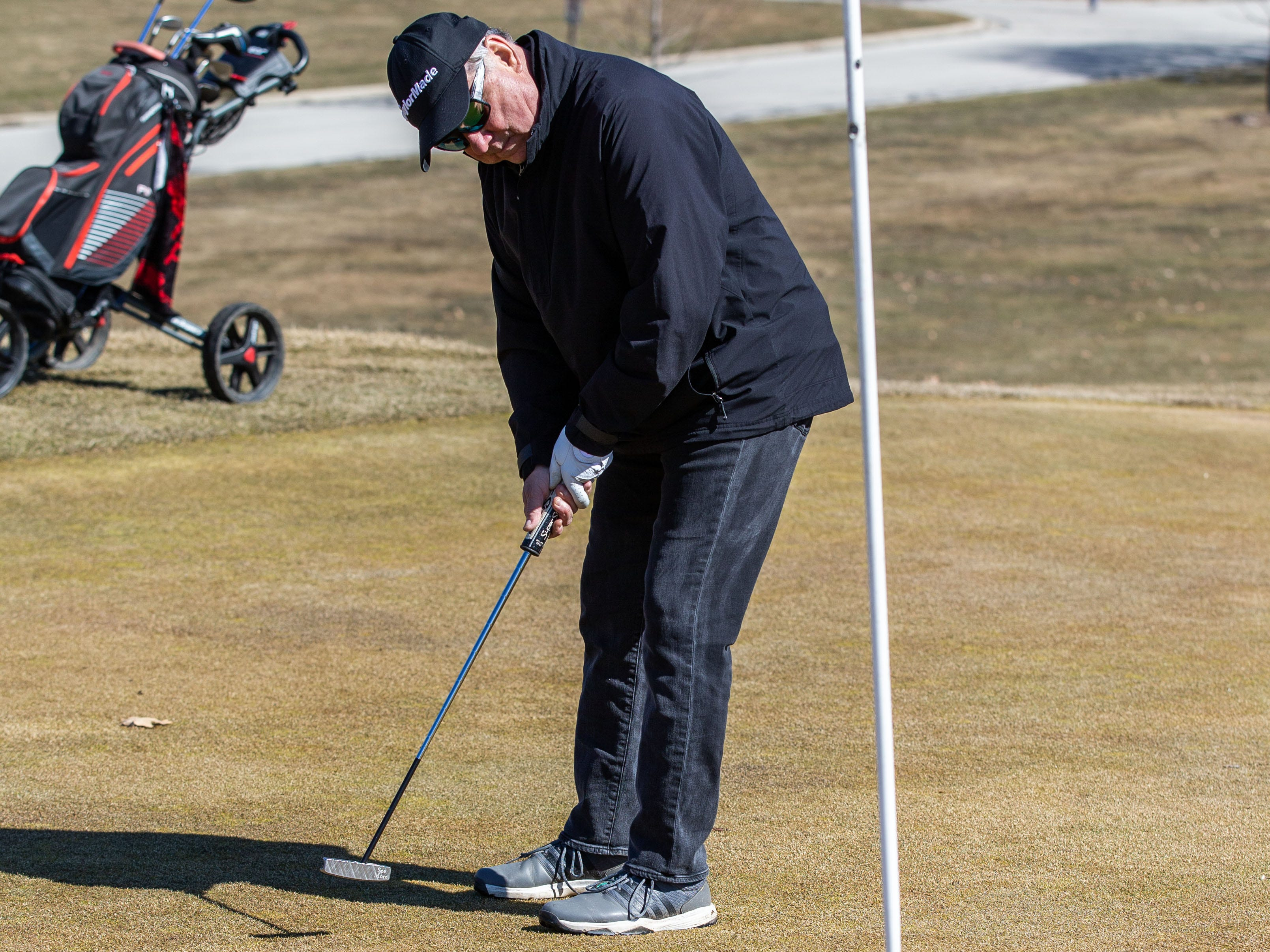 Chuck Wolf of West Allis sinks a putt at Whitnall Park Golf Course in Franklin on Saturday, March 23, 2019. Warm sunny weather lured many enthusiasts outside to enjoy the game.