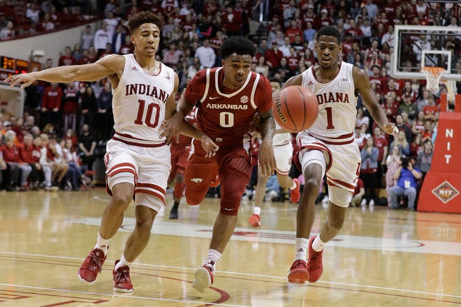 Arkansas's Desi Sills (0) chases a loose ball against Indiana's Rob Phinisee (10) and Aljami Durham (1) during the first half of a second round NIT Tournament, game Saturday in Bloomington, Ind.