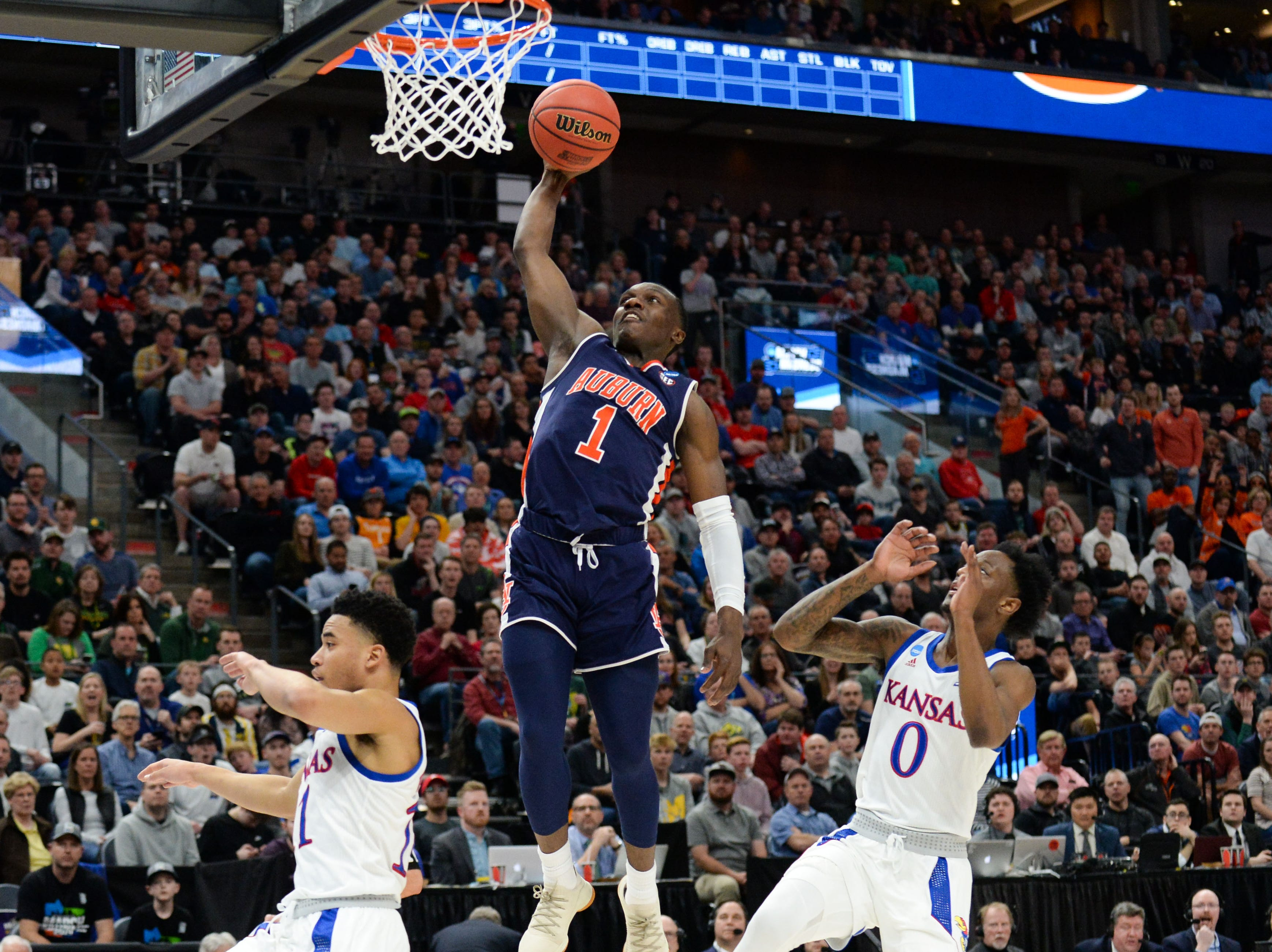 Mar 23, 2019; Salt Lake City, UT, USA; Auburn Tigers guard Jared Harper (1) goes up for a basket ahead of Kansas Jayhawks guard Marcus Garrett (0) during the first half in the second round of the 2019 NCAA Tournament at Vivint Smart Home Arena. Mandatory Credit: Gary A. Vasquez-USA TODAY Sports