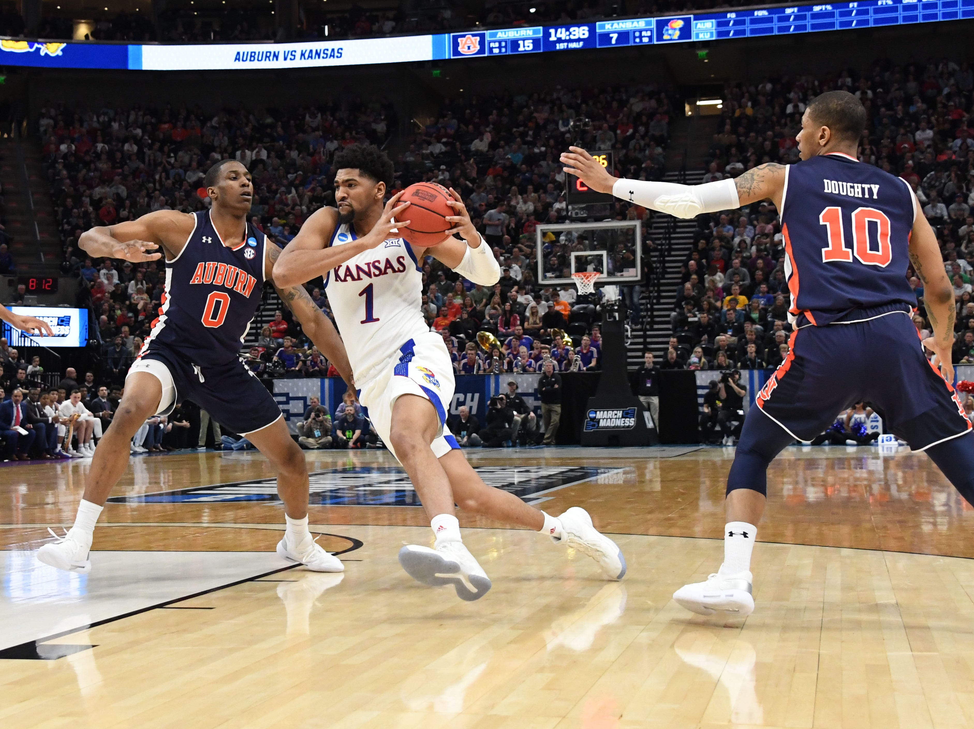 Mar 23, 2019; Salt Lake City, UT, USA; Kansas Jayhawks forward Dedric Lawson (1) drives through Auburn Tigers forward Horace Spencer (0) and guard Samir Doughty (10) during the first half in the second round of the 2019 NCAA Tournament at Vivint Smart Home Arena. Mandatory Credit: Kirby Lee-USA TODAY Sports