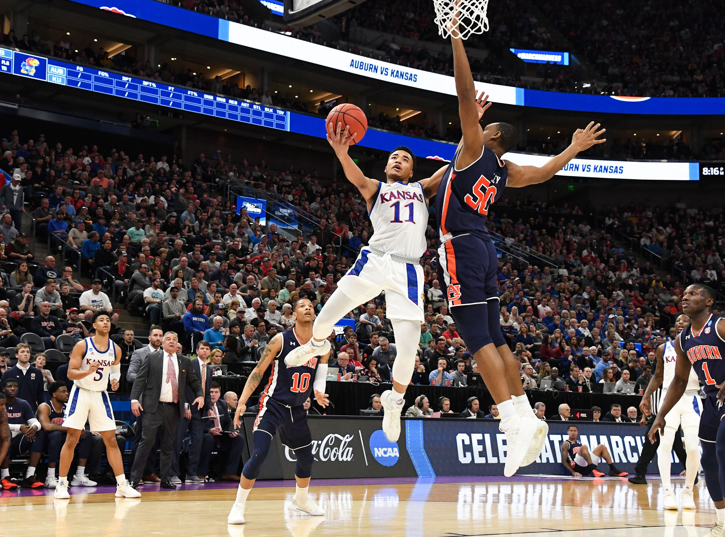 Mar 23, 2019; Salt Lake City, UT, USA; Kansas Jayhawks guard Devon Dotson (11) goes up for a shot as Auburn Tigers center Austin Wiley (50) defends during the first half in the second round of the 2019 NCAA Tournament at Vivint Smart Home Arena. Mandatory Credit: Kirby Lee-USA TODAY Sports