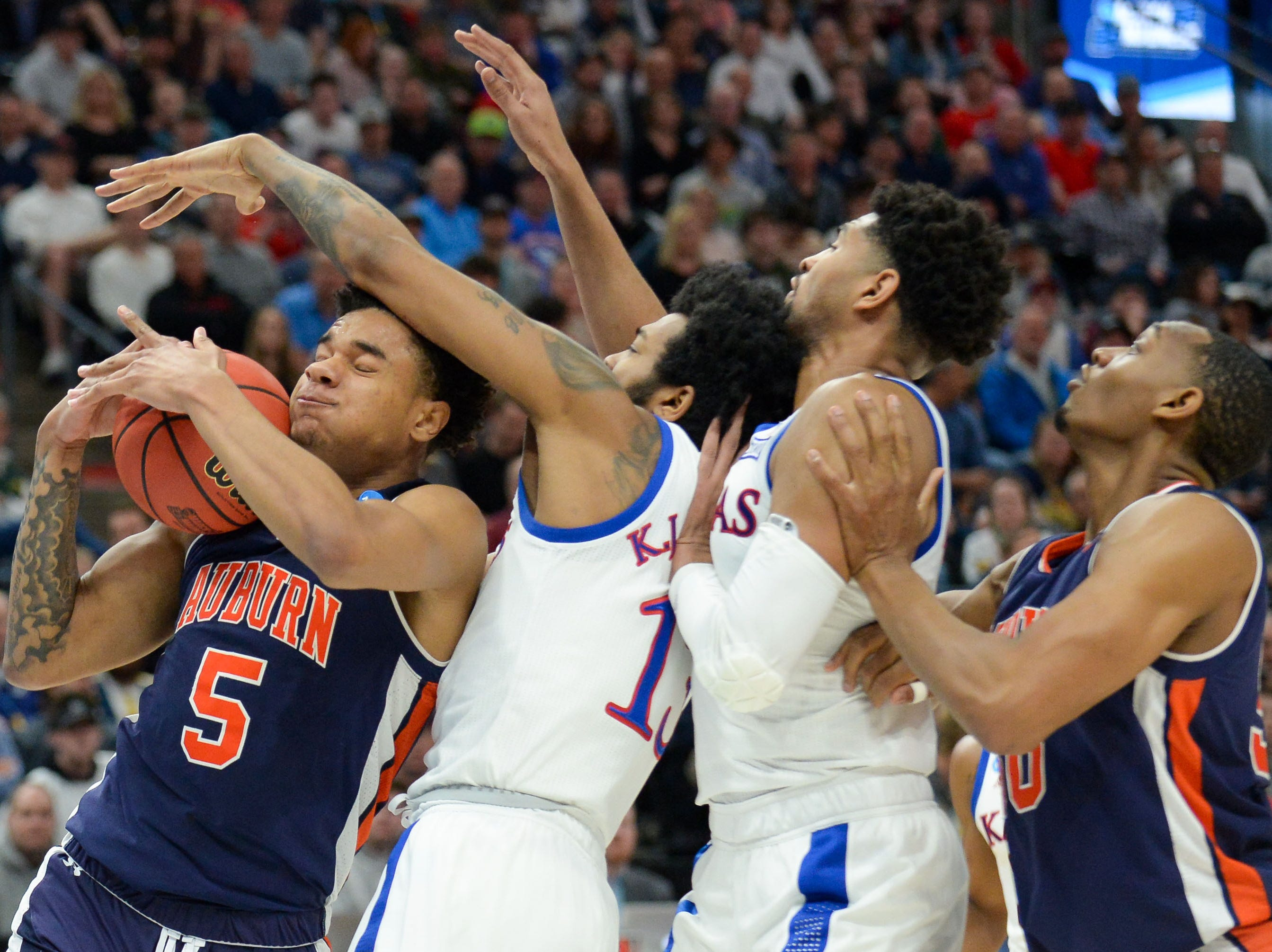 Mar 23, 2019; Salt Lake City, UT, USA; Auburn Tigers forward Chuma Okeke (5) holds onto the ball as he falls into Kansas Jayhawks guard K.J. Lawson (13) during the first half in the second round of the 2019 NCAA Tournament at Vivint Smart Home Arena. Mandatory Credit: Gary A. Vasquez-USA TODAY Sports