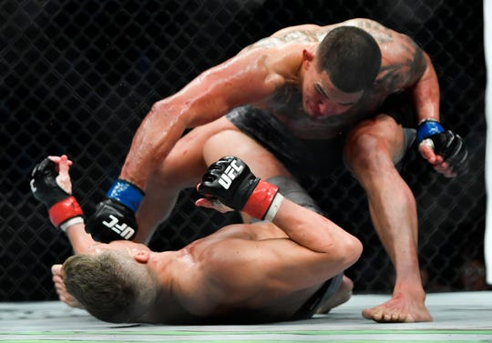 Anthony Pettis pounds Stephen Thompson on the mat after knocking Thompson out with his Superman punch in their welterweight bout during UFC Fight Night 148 at Bridgestone Arena Saturday, March 23, 2019 in Nashville, Tenn.