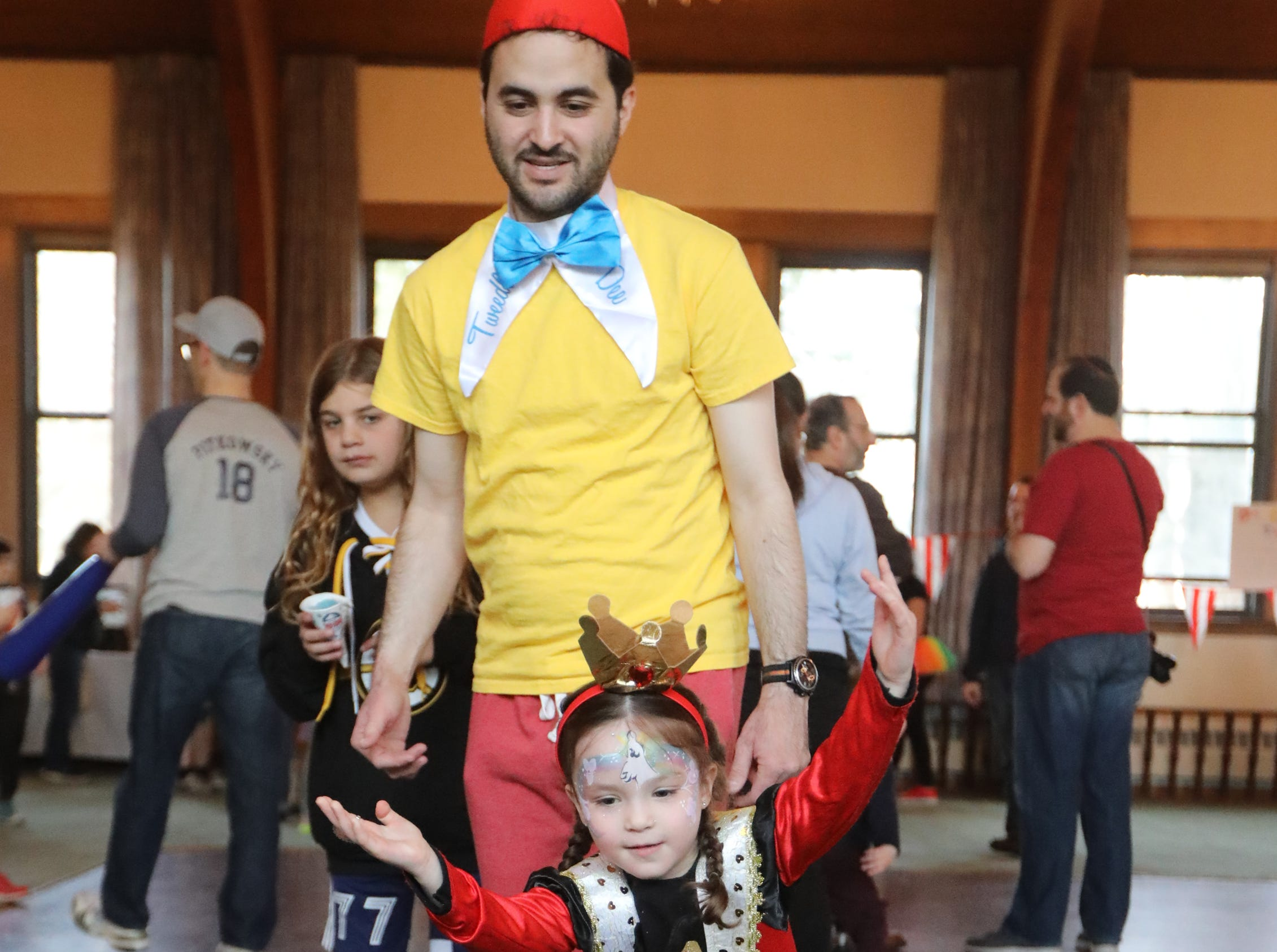Zahava Danzig, 4, dressed as, Queen of Hearts, bowls in front of her father, Michael Danzig, who is dressed as Tweedledee, at the Beth Sholom Annual Purim Carnival, in Teaneck.  Sunday, March 24, 2019