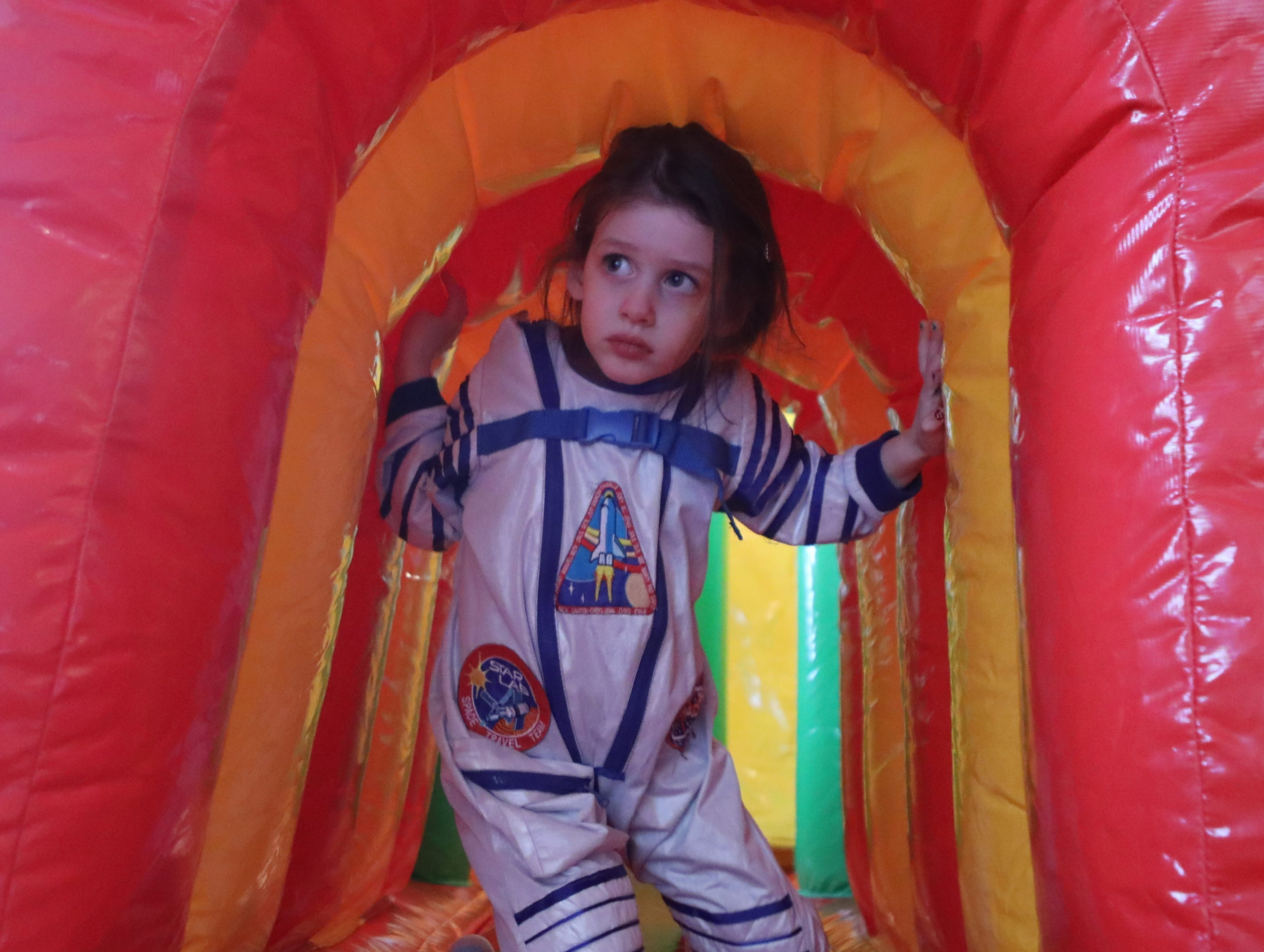 Meirav Liben, 4, dressed as an astronaut, emerges from an inflatable obstacle course, at the Beth Sholom Annual Purim Carnival, in Teaneck.  Sunday, March 24, 2019