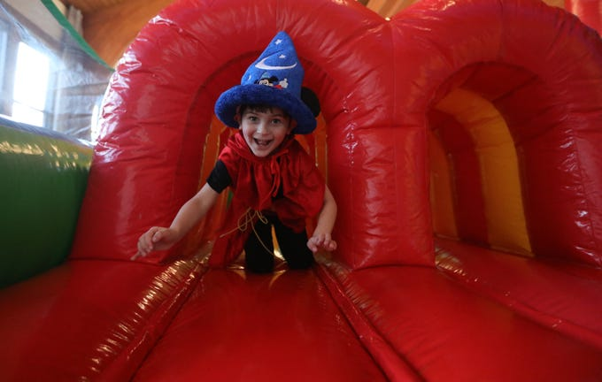 Benci Skoff, 4, dressed as Sorcerer Mickey, emerges from an inflatable obstacle course, at the Beth Sholom Annual Purim Carnival, in Teaneck.  Sunday, March 24, 2019