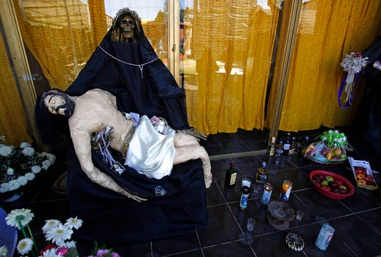"In this March 1, 2017 file photo, a statue of La Santa Muerte, or ""Our Lady of Holy Death,"" holds a statue of Jesus on an altar inside a temple dedicated to Santa Muerte, on the outskirts Mexico City in the State of Mexico. Santa Fe Archbishop John Wester in Albuquerque, New Mexico, recently told The Associated Press he believes some Catholics may be fooled into venerating Santa Muerte even though the focus on death runs counter to the church's teachings and she's not an official Catholic saint."