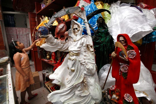 "In this Feb. 19, 2017 file photo, a child arranges statues of La Santa Muerte, or ""Our Lady of Holy Death,"" on the edge of Mexico City's Tepito neighborhood."