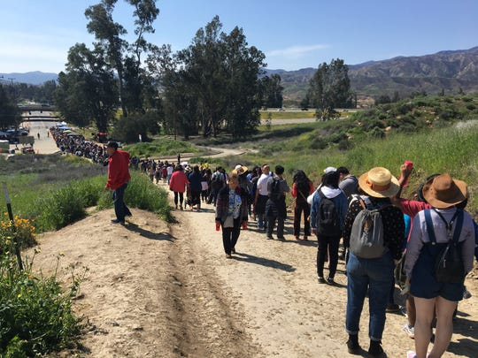 Hundreds of poppy enthusiasts wait in line to catch shuttles back to their cars. Visitors to Walker Canyon in Lake Elsinore are no longer allowed to park near the poppy fields on weekends.