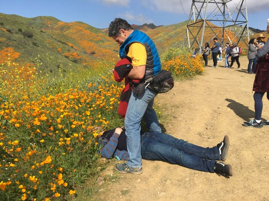 Roy Wallack takes a photo of his son, Joseph, who has his head on a dirt patch surrounded by poppies. They were among the thousands who visited Walker Canyon in Lake Elsinore to see the flowers.